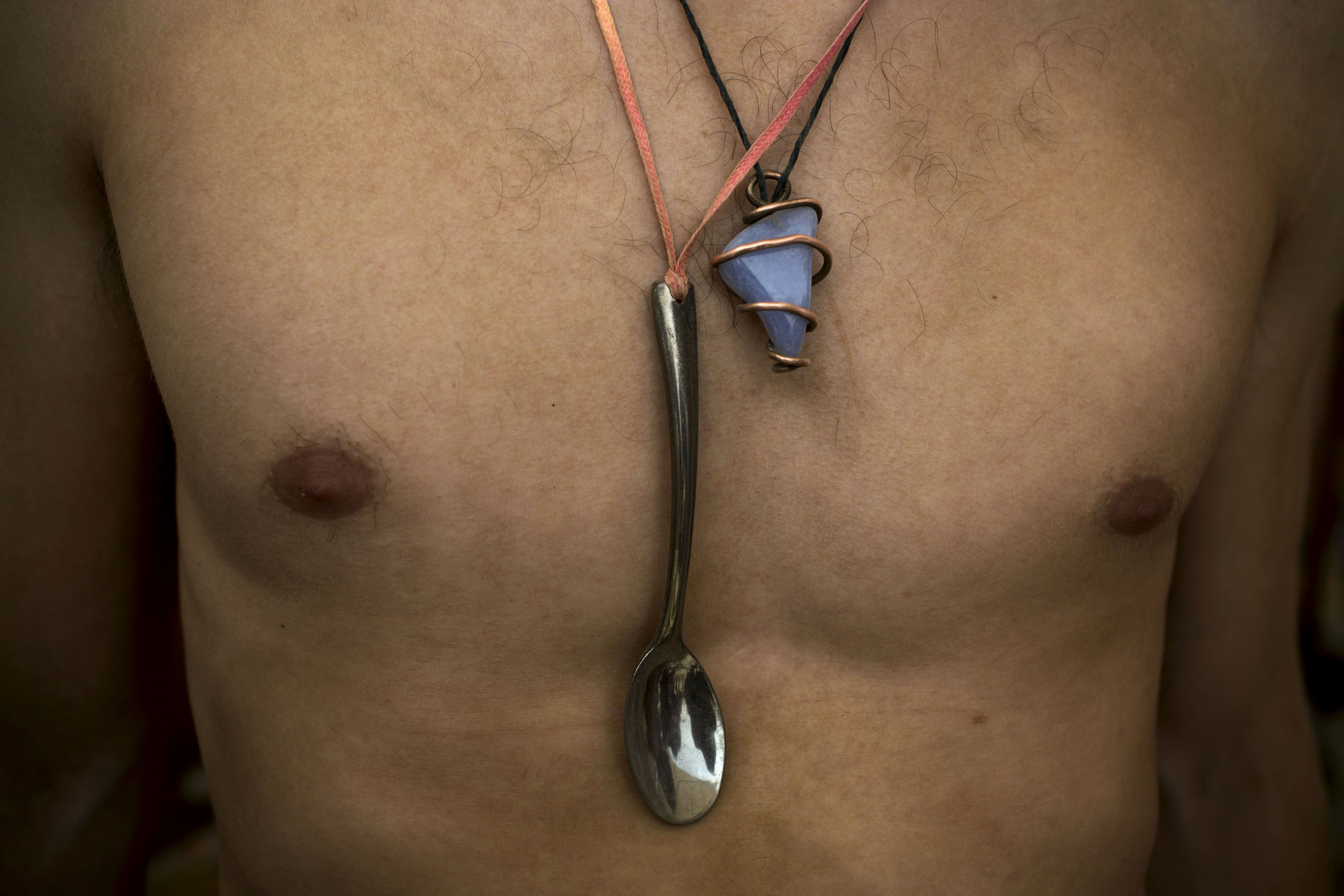 An Israeli man wears a spoon and a stone as necklaces as he dances during a party at Israel''s first Midburn festival in the Negev Desert, Israel on June 5, 2014.