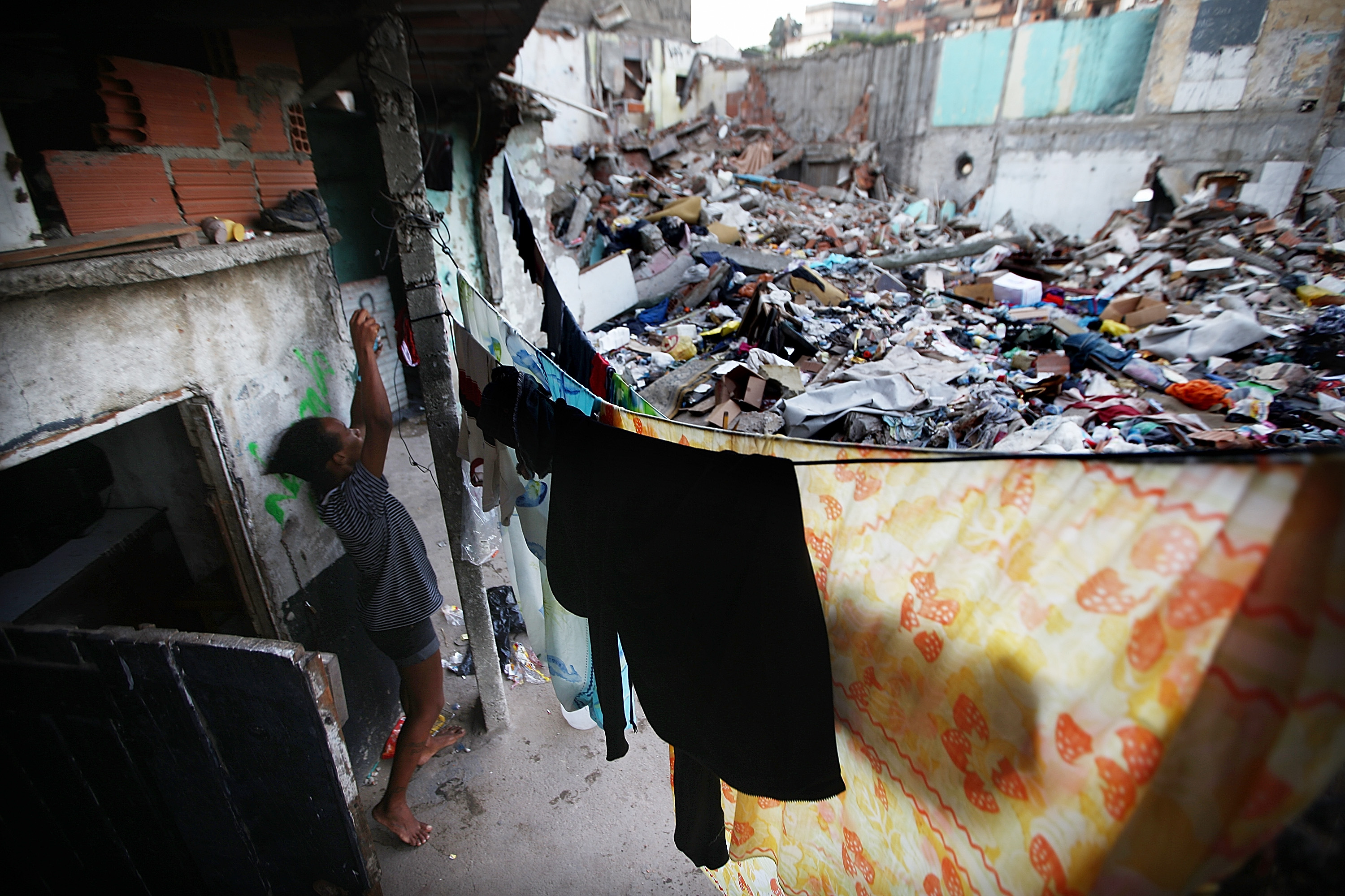 A woman hangs laundry next to the remains of demolished homes in the Metro Mangueira favela, located near Maracana stadium, on May 22, 2014 in Rio de Janeiro.