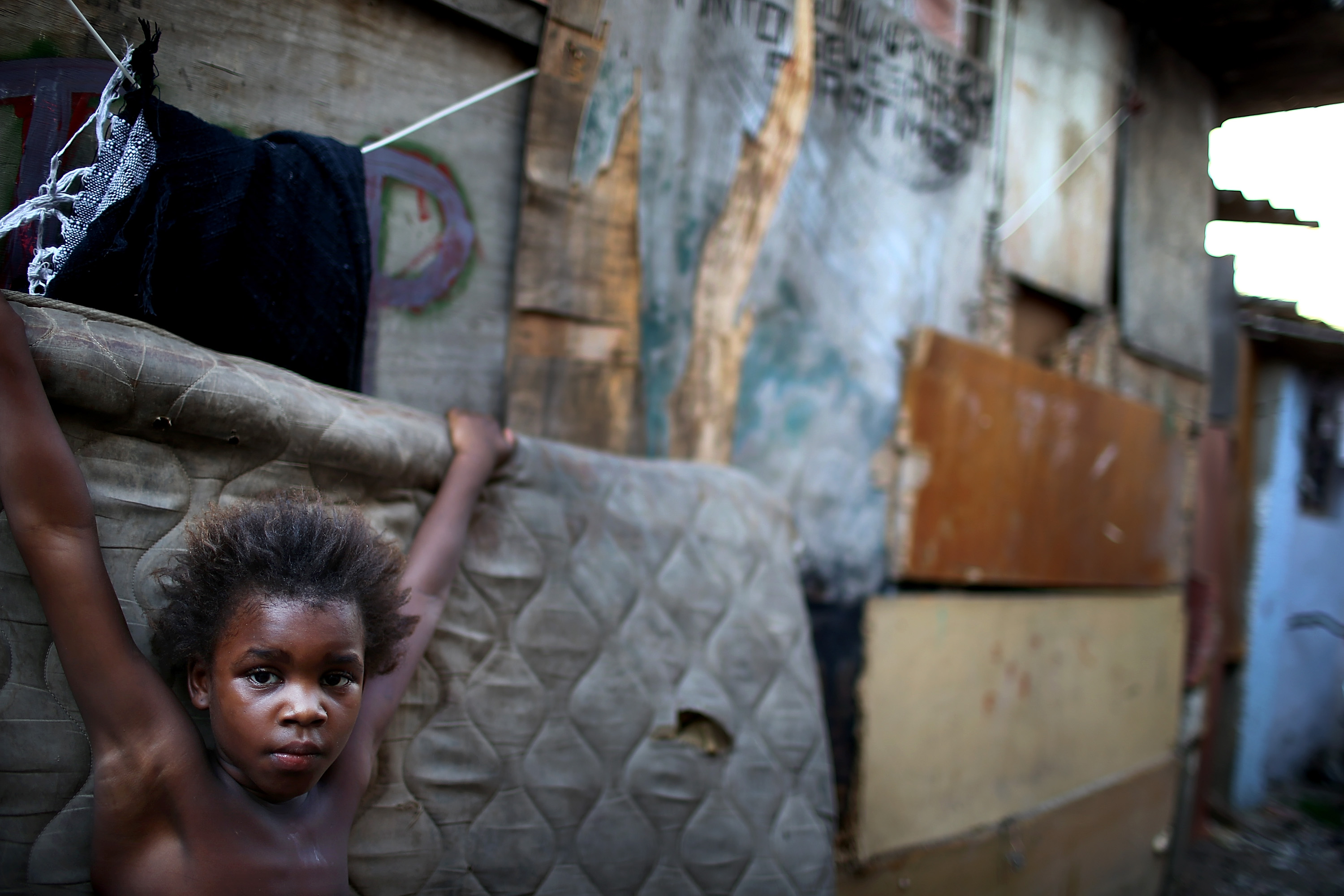 Resident Leiticia stands in an impoverished area in the unpacified Complexo da Mare slum complex, one of the largest favela complexes in Rio, on March 18, 2014 in Rio de Janeiro.