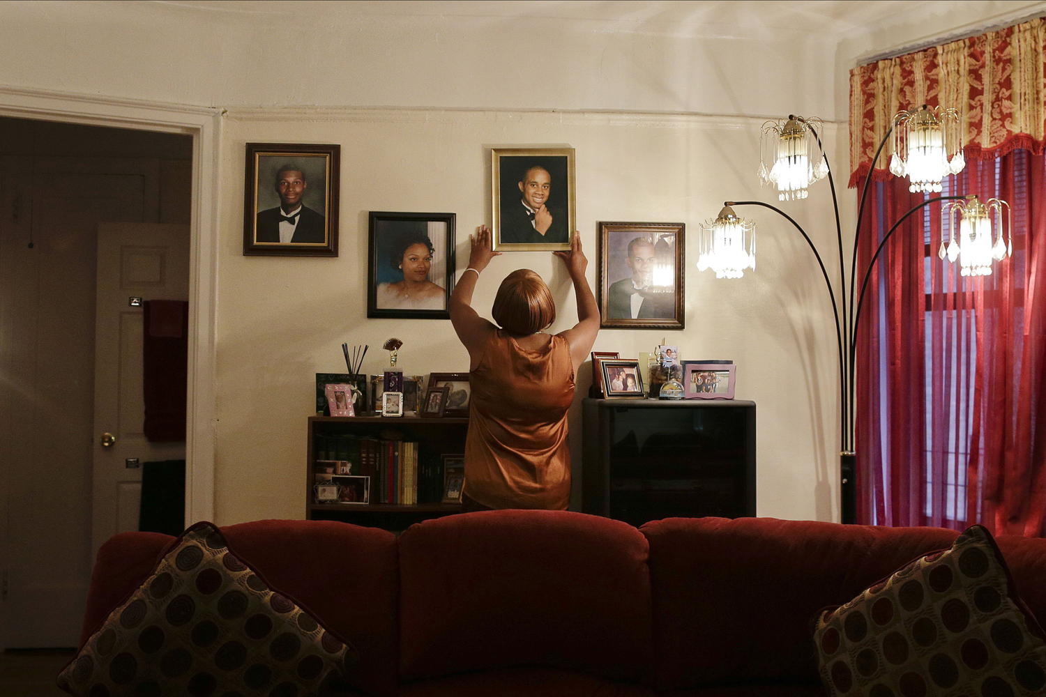 Jun. 25, 2014. Tracie Morales places a photo of her son, Jamal Polo, back up on a wall at her home, in New York. Polo committed suicide in May 2012 while jailed on sexual misconduct charges.