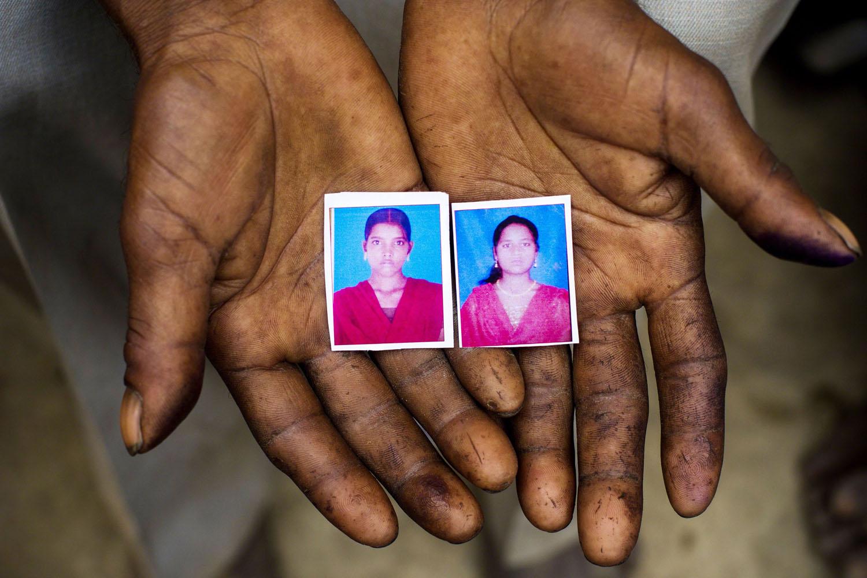 May 30,  2014. Sohan Lal (55) holds passport sized images in his hands of his daughter Murti (right) and niece Pushpa (left) in Katra Sadatganj village,Ushait near Baduan, Uttar Pradesh, India.