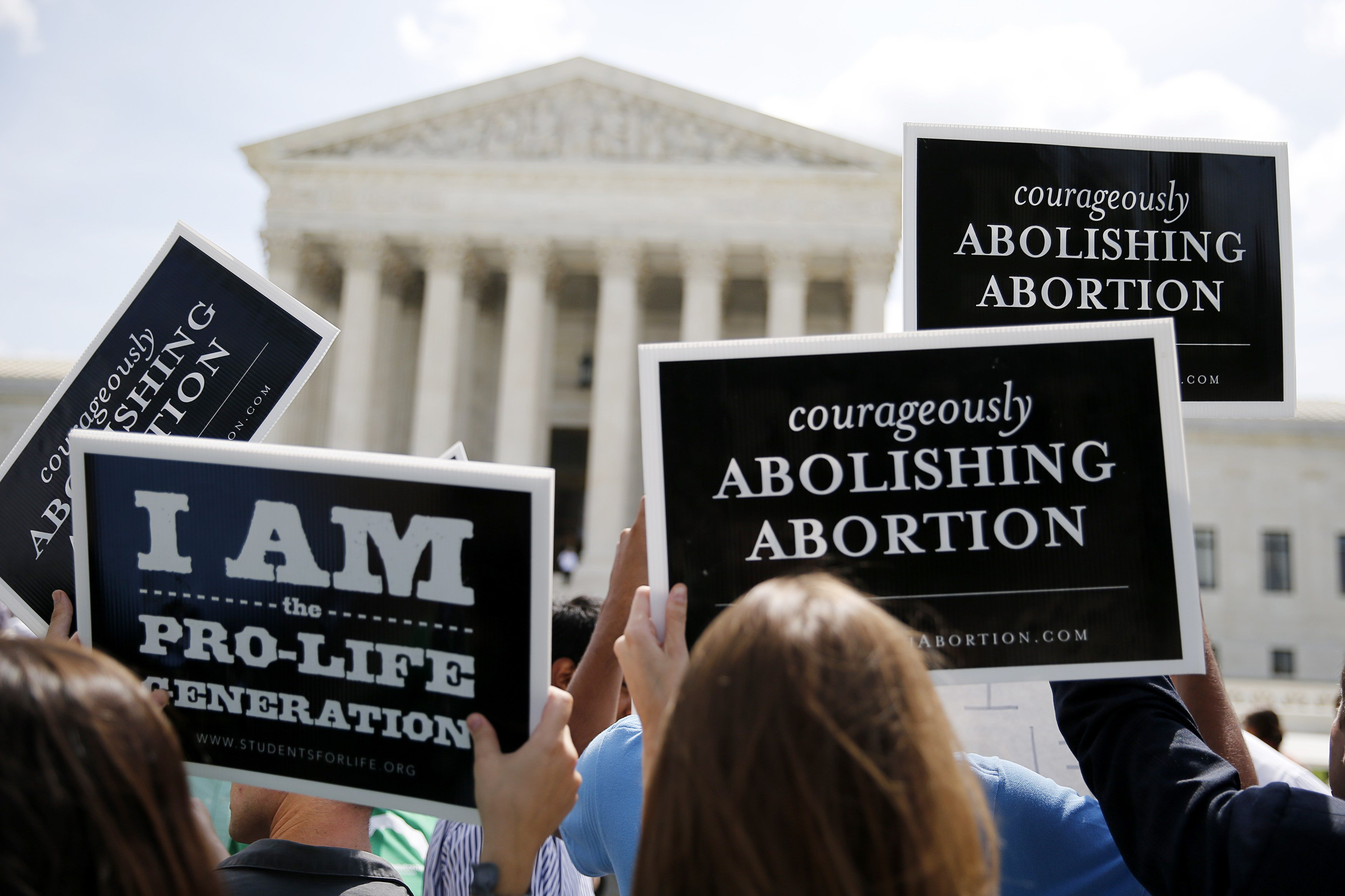 Anti-abortion protestors celebrate the U.S. Supreme Court's ruling striking down a Massachusetts law that mandated a protective buffer zone around abortion clinics,  outside the Supreme Court in Washington June 26, 2014.
