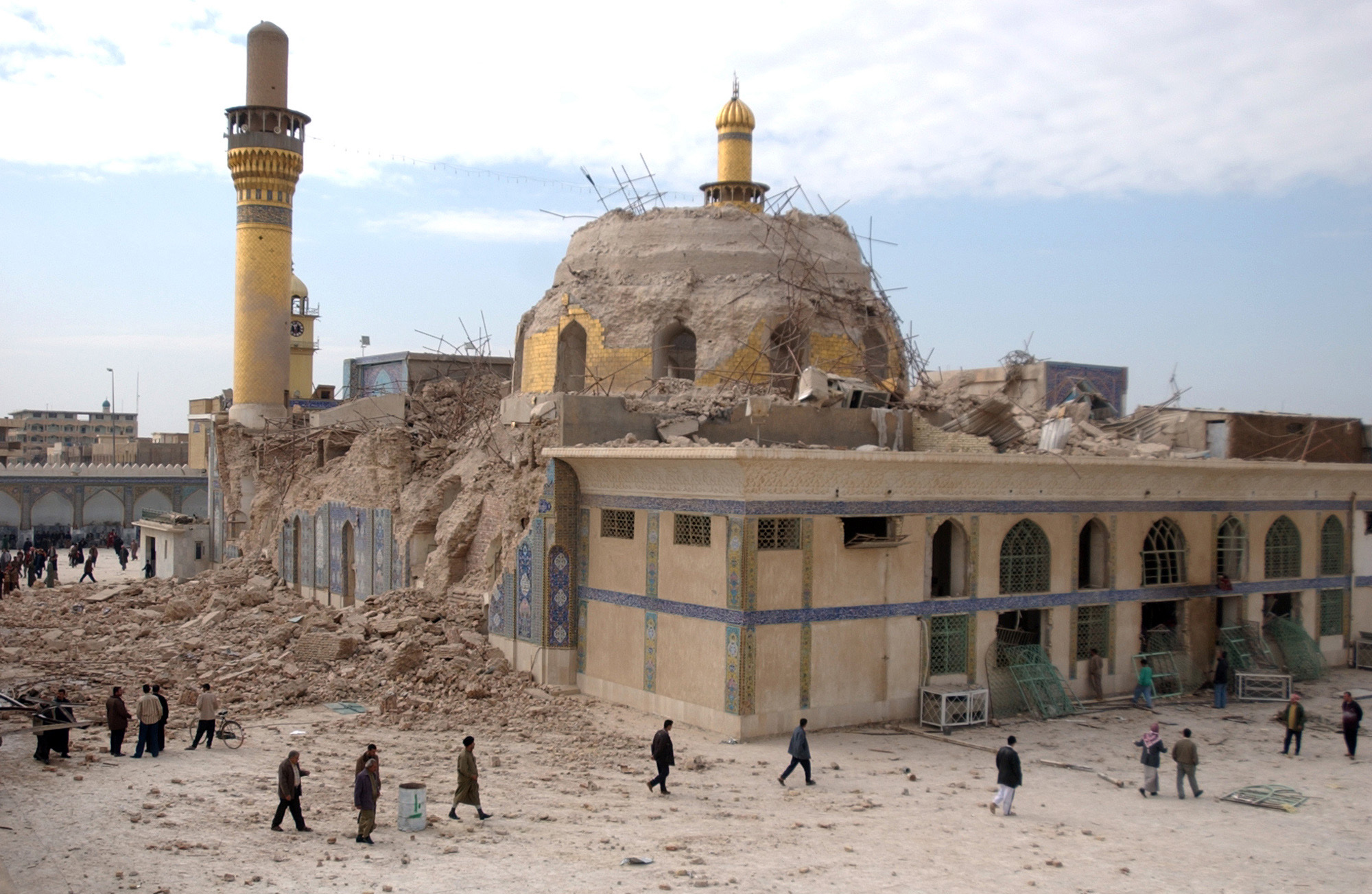 Iraqis walk past the damaged al-Askari mosque following an explosion in Samarra, 95 kilometers (60 miles) north of Baghdad, Iraq on Feb. 22, 2006.