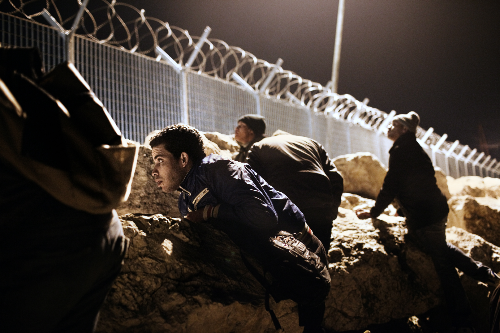Mohamed from Morocco and his friends hiding and waiting for the right moment to illegally board a ship to Italy. 2012. Corinth, Greece.