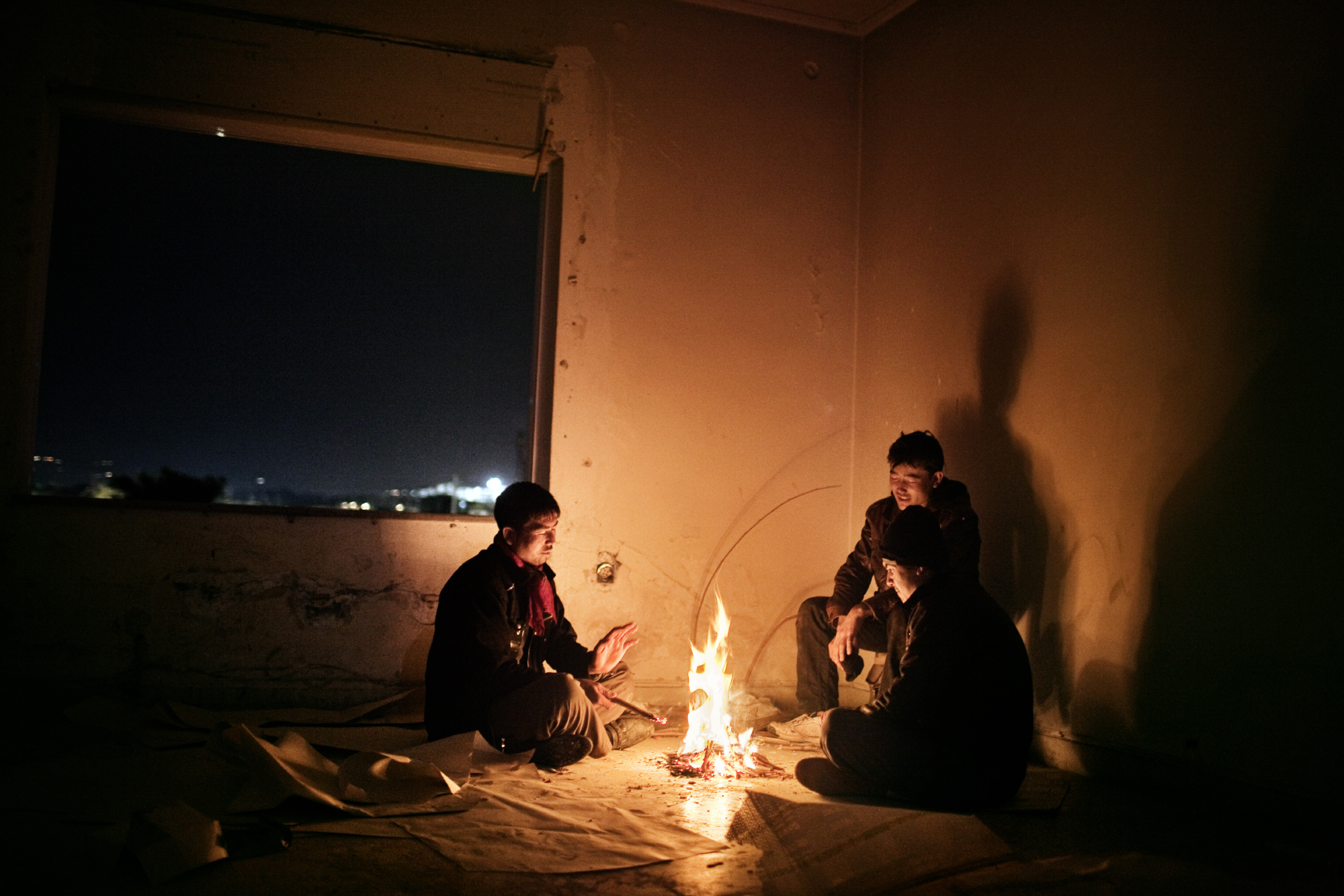 Three young Afghans spend the night in an abandoned building near the beach of Patras, Greece.