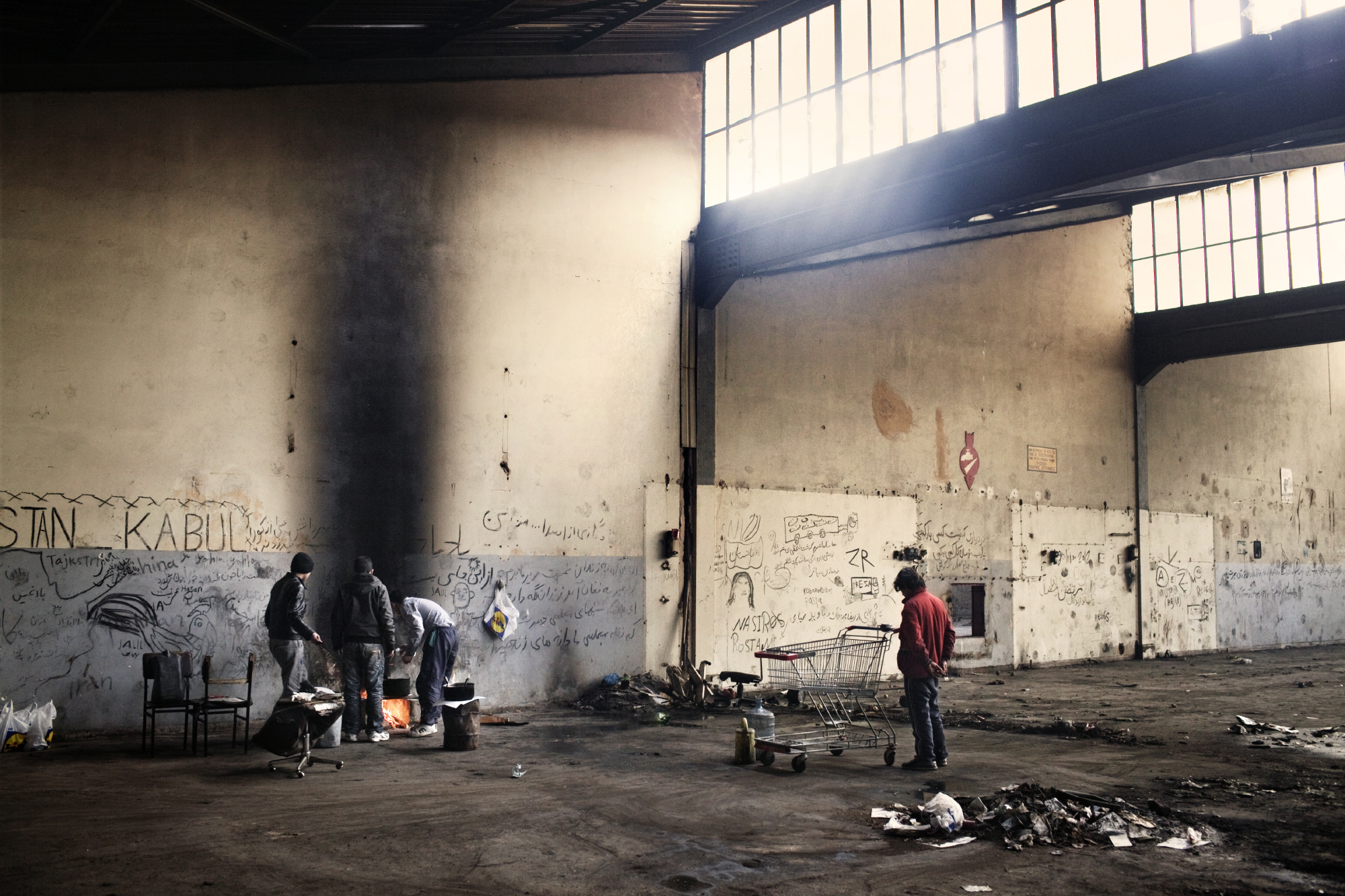 Young Afghans cooking in an abandoned factory in Patras, Greece.
