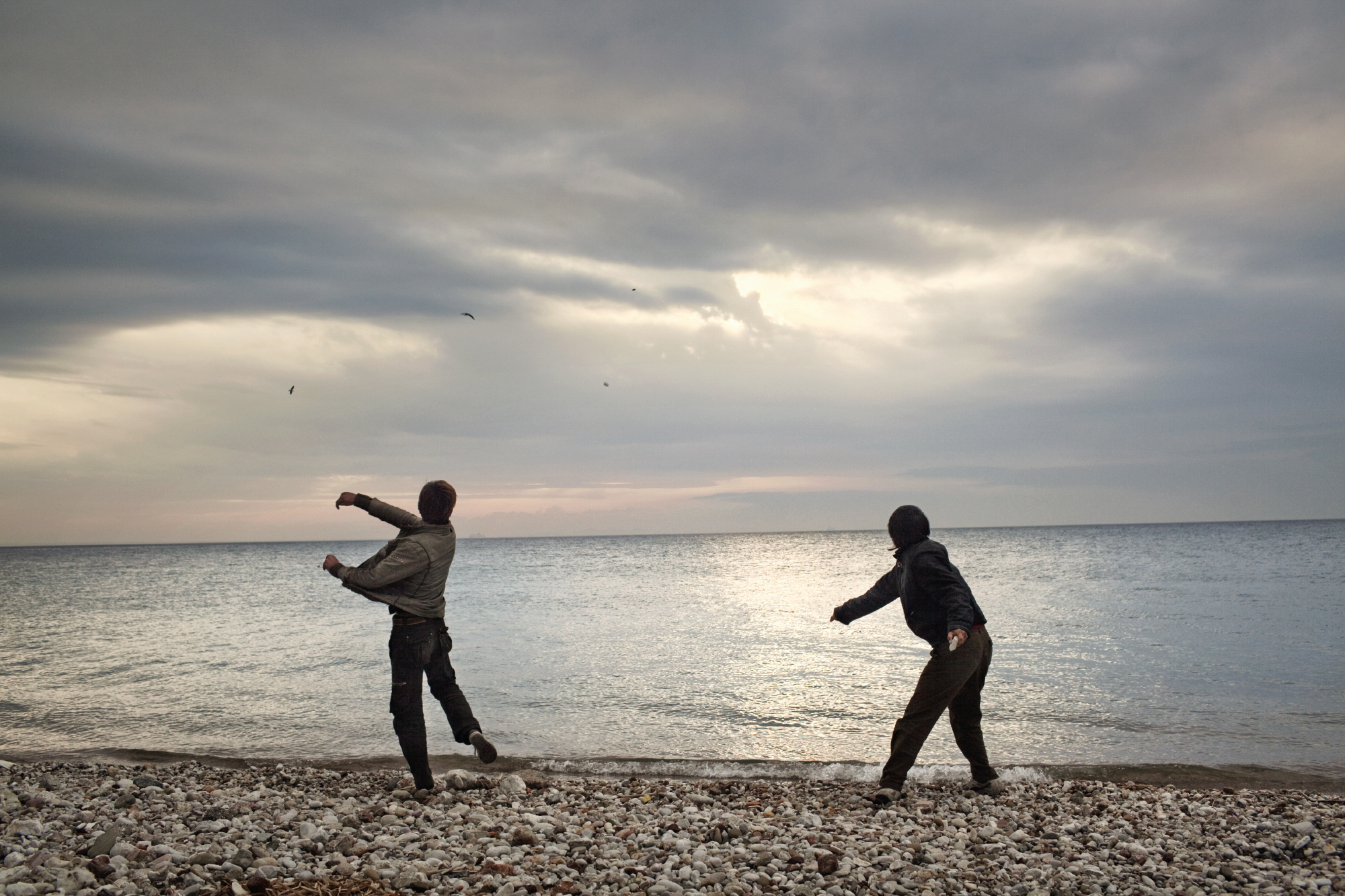 Afghan boys throwing stones into the sea in Patras, Greece. They are waiting for the evening, when they will try to sneak into the port to board a ship bound for Italy.