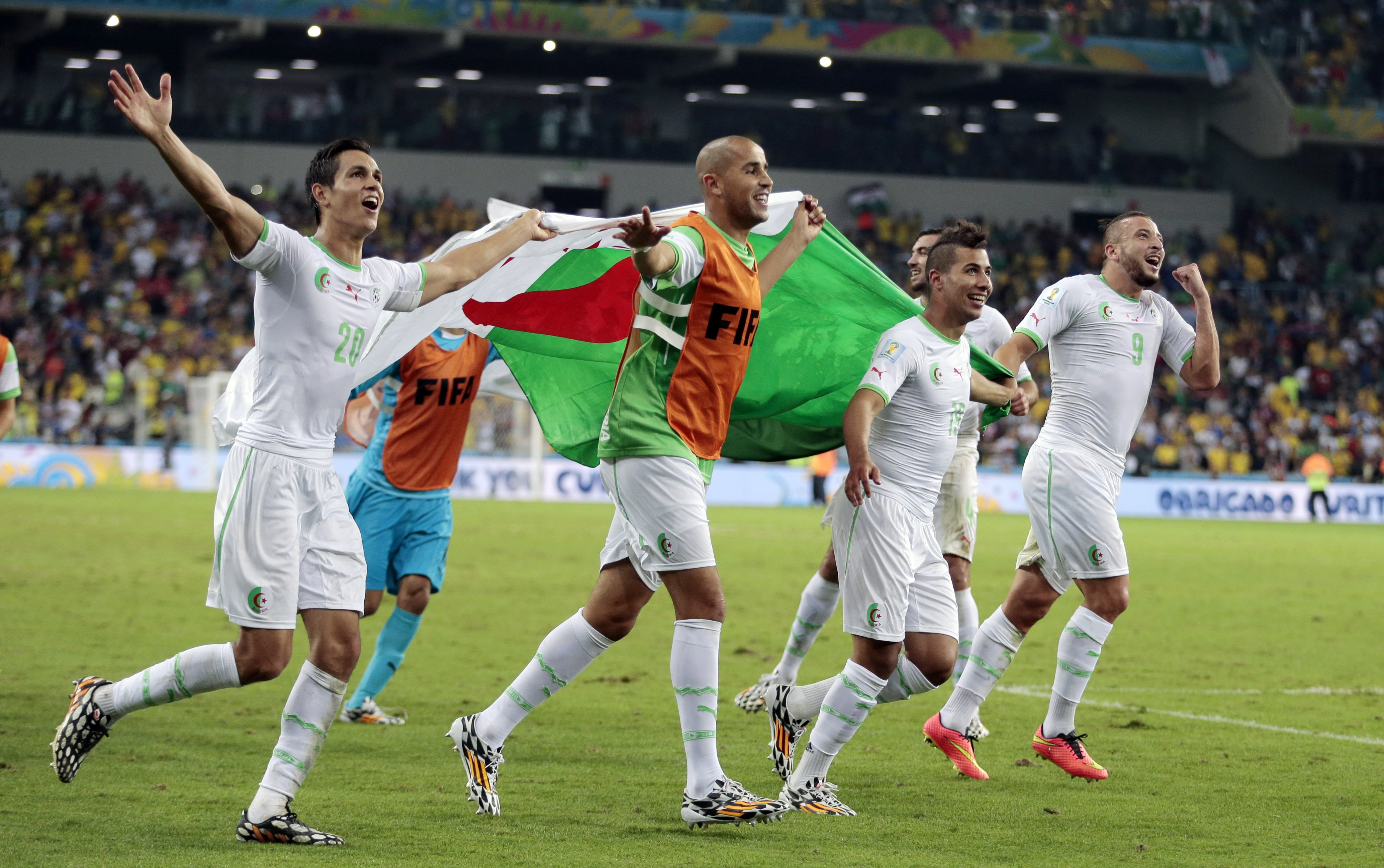 Algerian players celebrate after the group H World Cup soccer match between Algeria and Russia at the Arena da Baixada in Curitiba, Brazil on June 26, 2014.