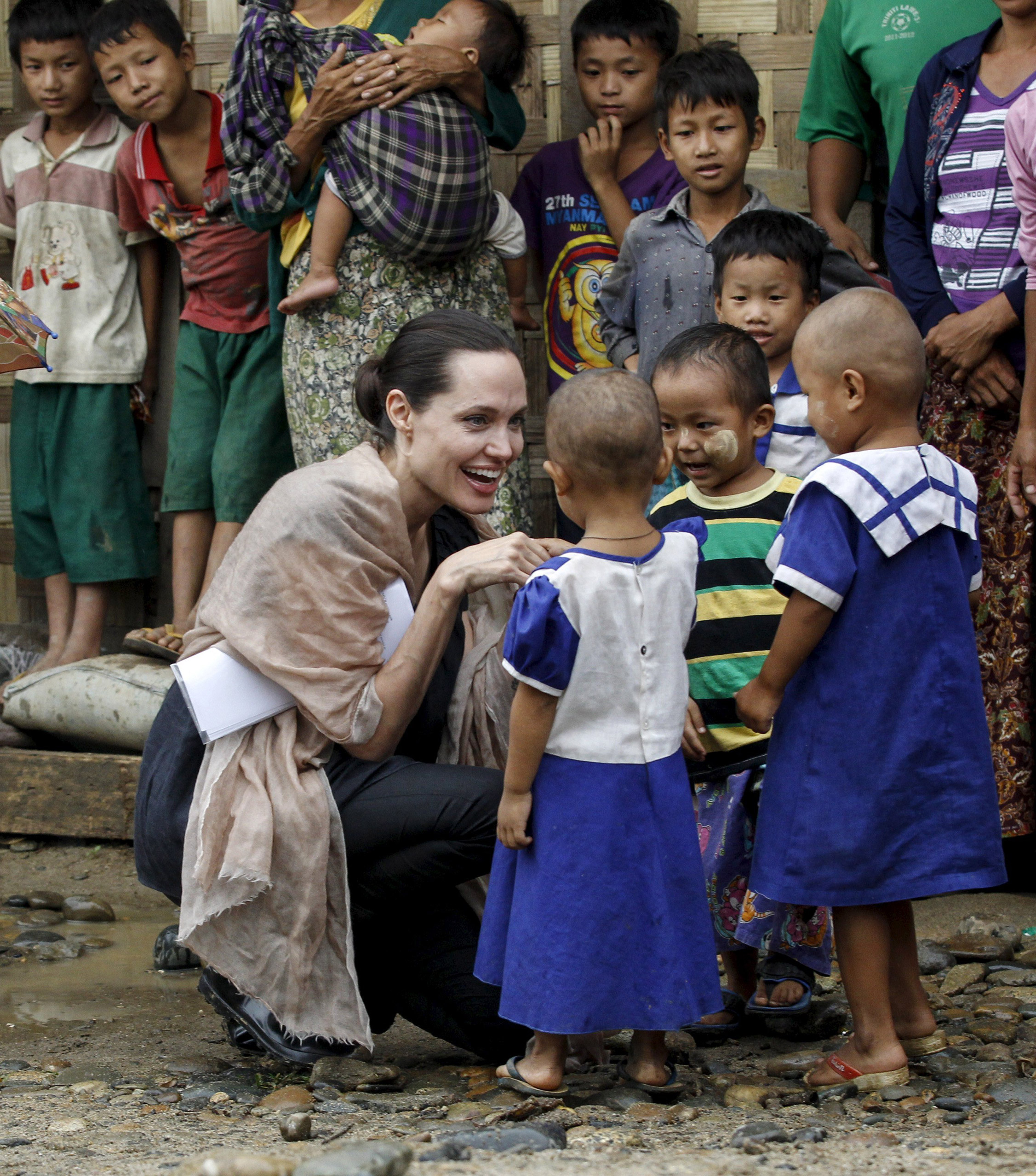 UNHCR special envoy Angelina Jolie Pitt shakes hands with Kachin ethnic refugee children as she visits Eight Miles Palana IDP camp in Myitkyina capital city of Kachin state, Myanmar on July 30, 2015.