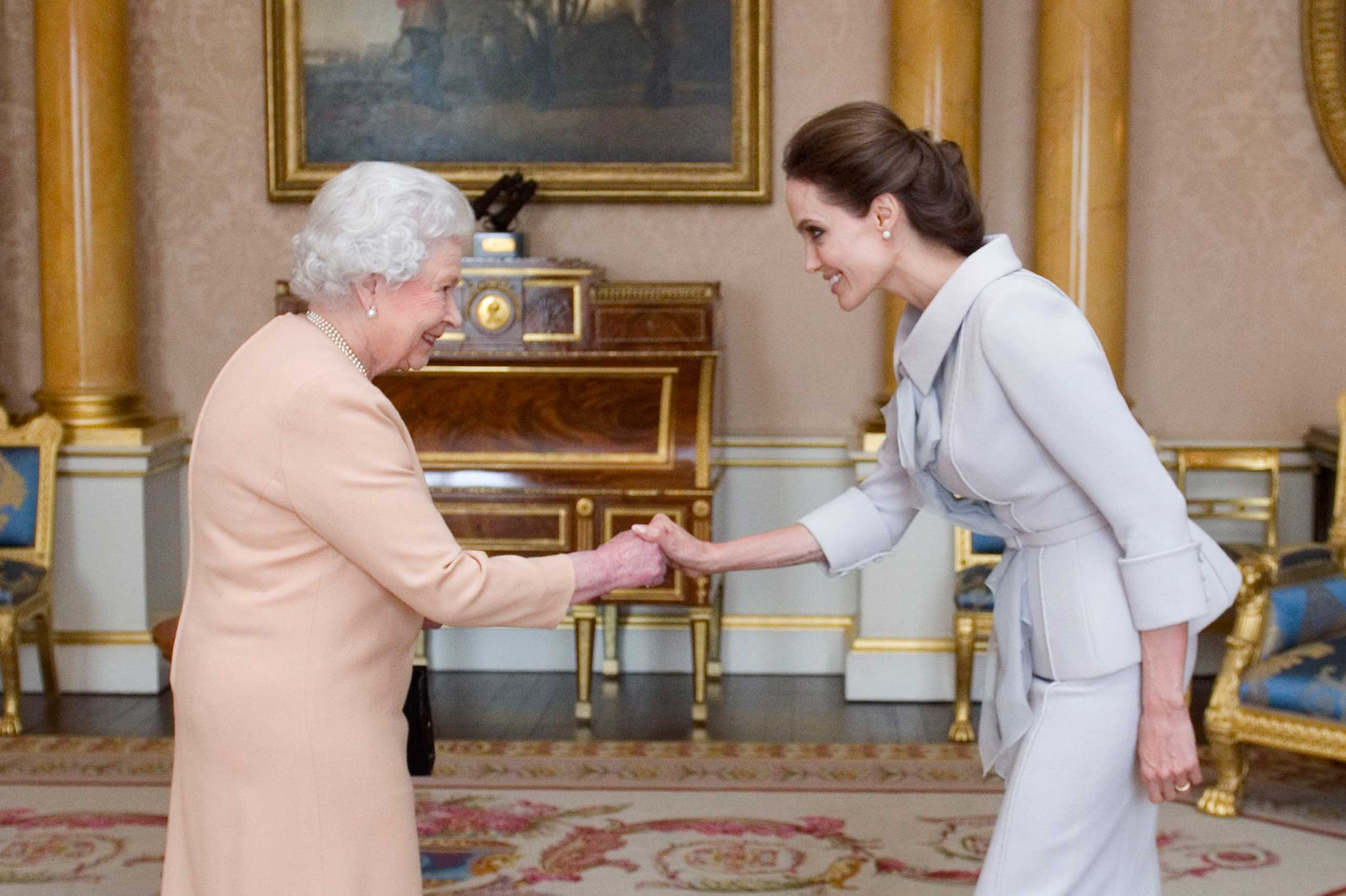 Actress Angelina Jolie, right, is presented with the Insignia of an Honorary Dame Grand Cross of the Most Distinguished Order of St Michael and St George by Britain's Queen Elizabeth II at Buckingham Palace, London, Oct. 10, 2014.