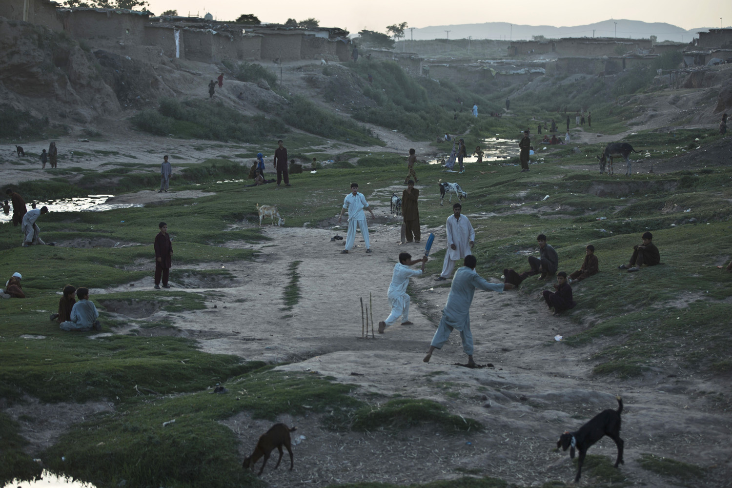 Internally Displaced Pakistanis from tribal areas and Afghan refugees play cricket, on the outskirts of Islamabad, Pakistan on  June 3, 2014.