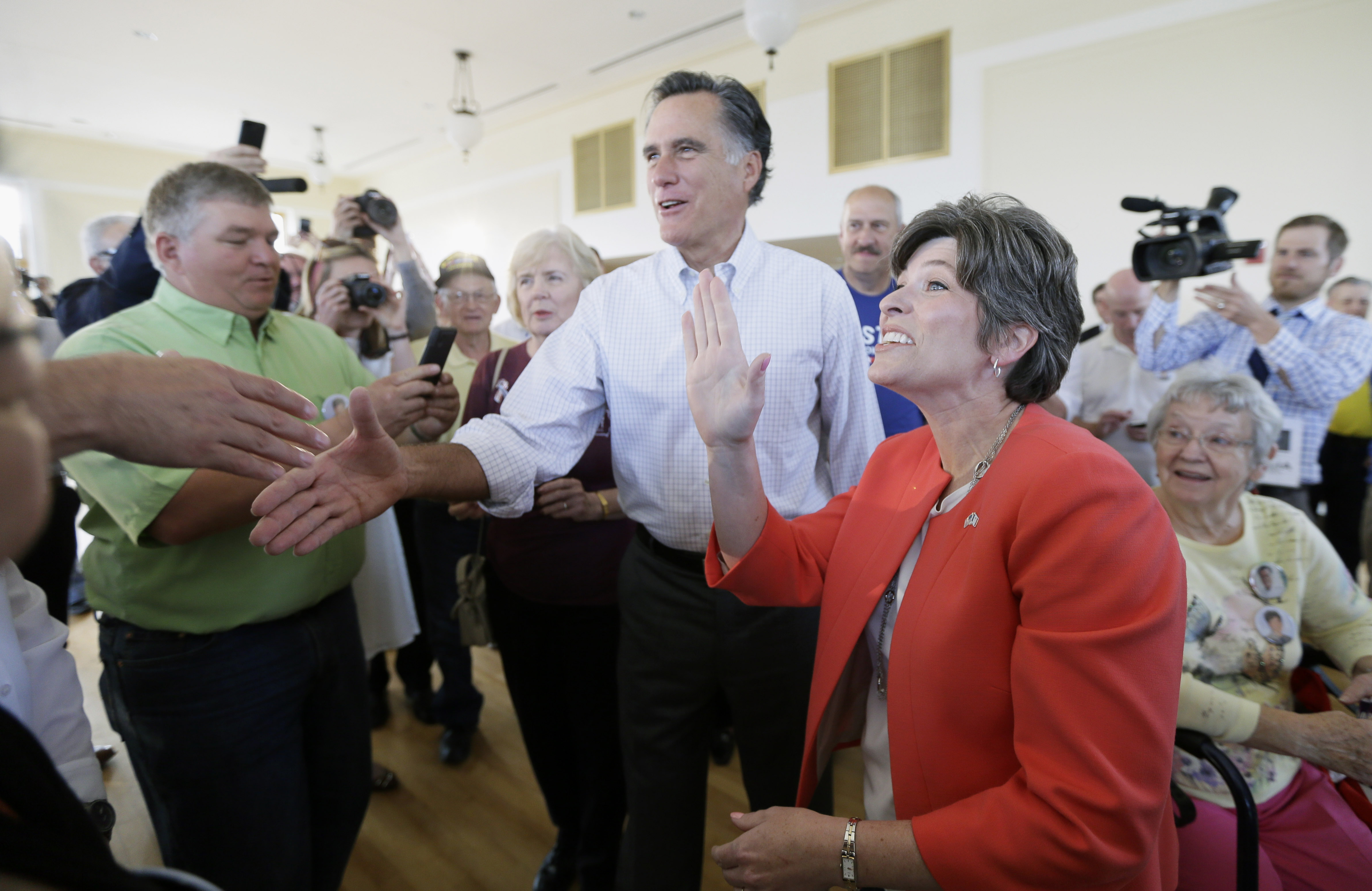 Former Republican presidential nominee Mitt Romney, center, greets supporters during a rally for Iowa Republican Senate candidate Joni Ernst, right, Friday, May 30, 2014, in Cedar Rapids, Iowa.