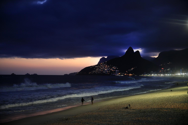 A couple walks on the Ipanema beach at night  in Rio de Janeiro on June 4, 2014.