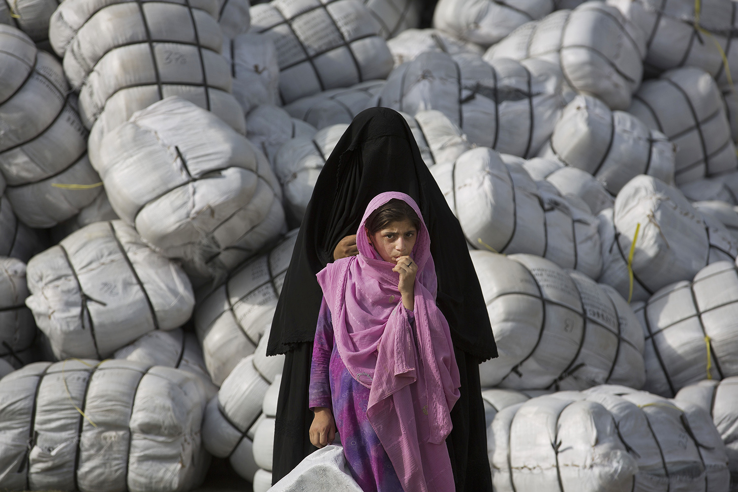 June 27, 2014. A displaced Pakistani mother and daughter wait to get relief supplies at a distribution center in Bannu, Pakistan.