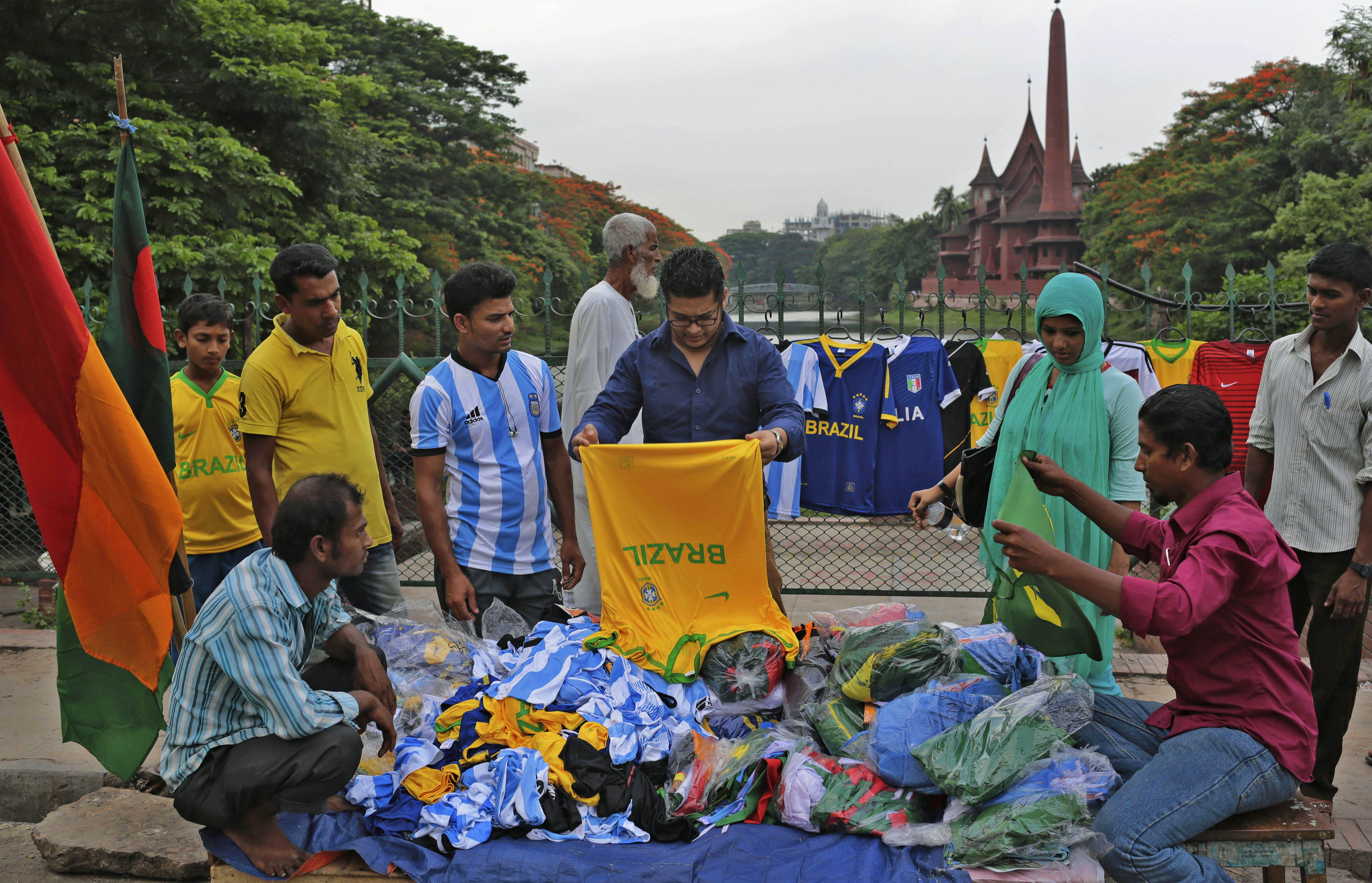 A man examines a T-shirt in the style of Brazil's national soccer team, being offered by a street vendor in Dhaka, Bangladesh, on June 1, 2014