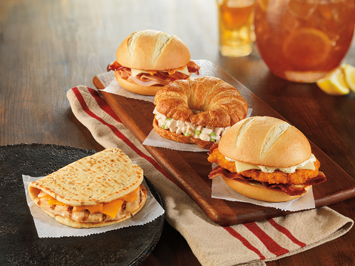 This product image provided by Dunkin' Donuts shows the chain's Grilled Chicken Flatbread, left, and bakery sandwich line.