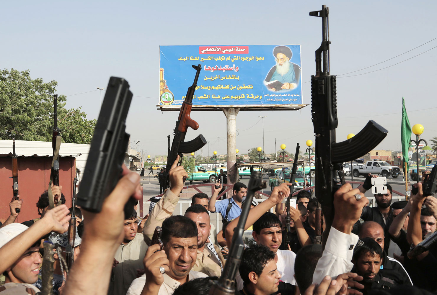 Iraqi Shiite tribal fighters raise their weapons and chant slogans against the al-Qaida-inspired Islamic State of Iraq and the Levant below a portrait of Ayatollah Ali al-Sistani, in Baghdad's Sadr City, Iraq, June 18, 2014. On Friday, Grand Ayatollah Ali al-Sistani, Iraq's top Shiite cleric, called for a new effective government in Iraq.