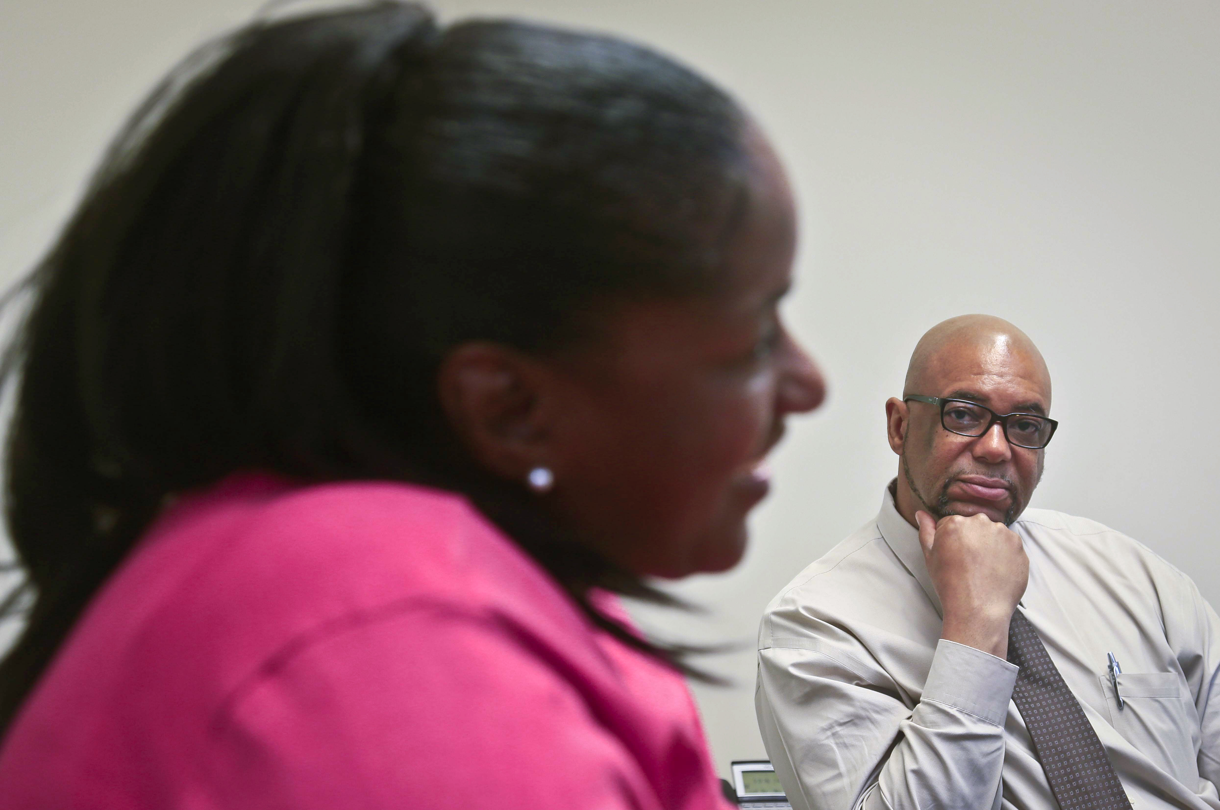 In this May 29, 2014 photo, Stan Richards, right, an executive with the Fortune Society, listens as Melissa Carter, left, speaks during an interview in New York.