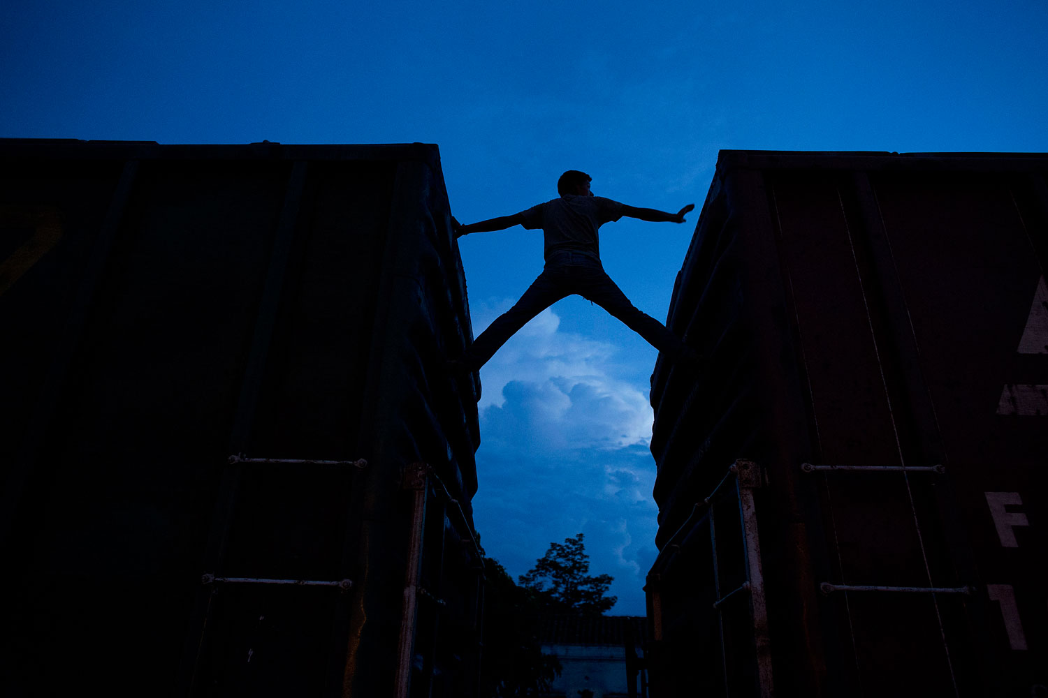 A Central American migrant practices scaling parked boxcars as he awaits the arrival of a northbound freight train in Arriaga, Mexico, on June 19, 2014.