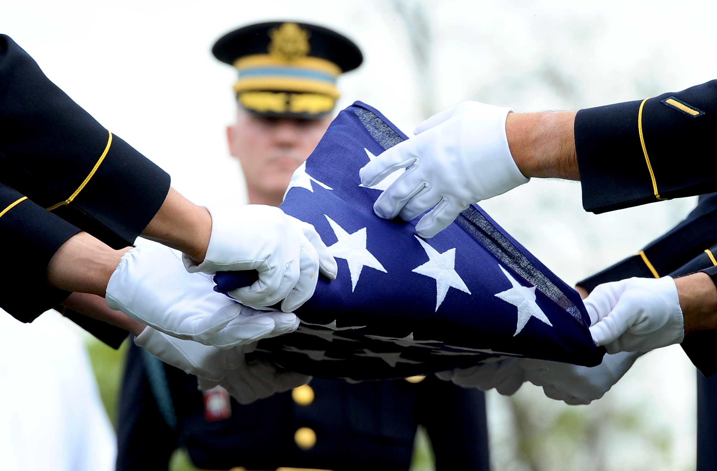 Members of The Old Guard fold the flag during the burial service for a U.S. soldier killed in combat. The service was held at Arlington National Cemetery in Va. on April 17, 2013.