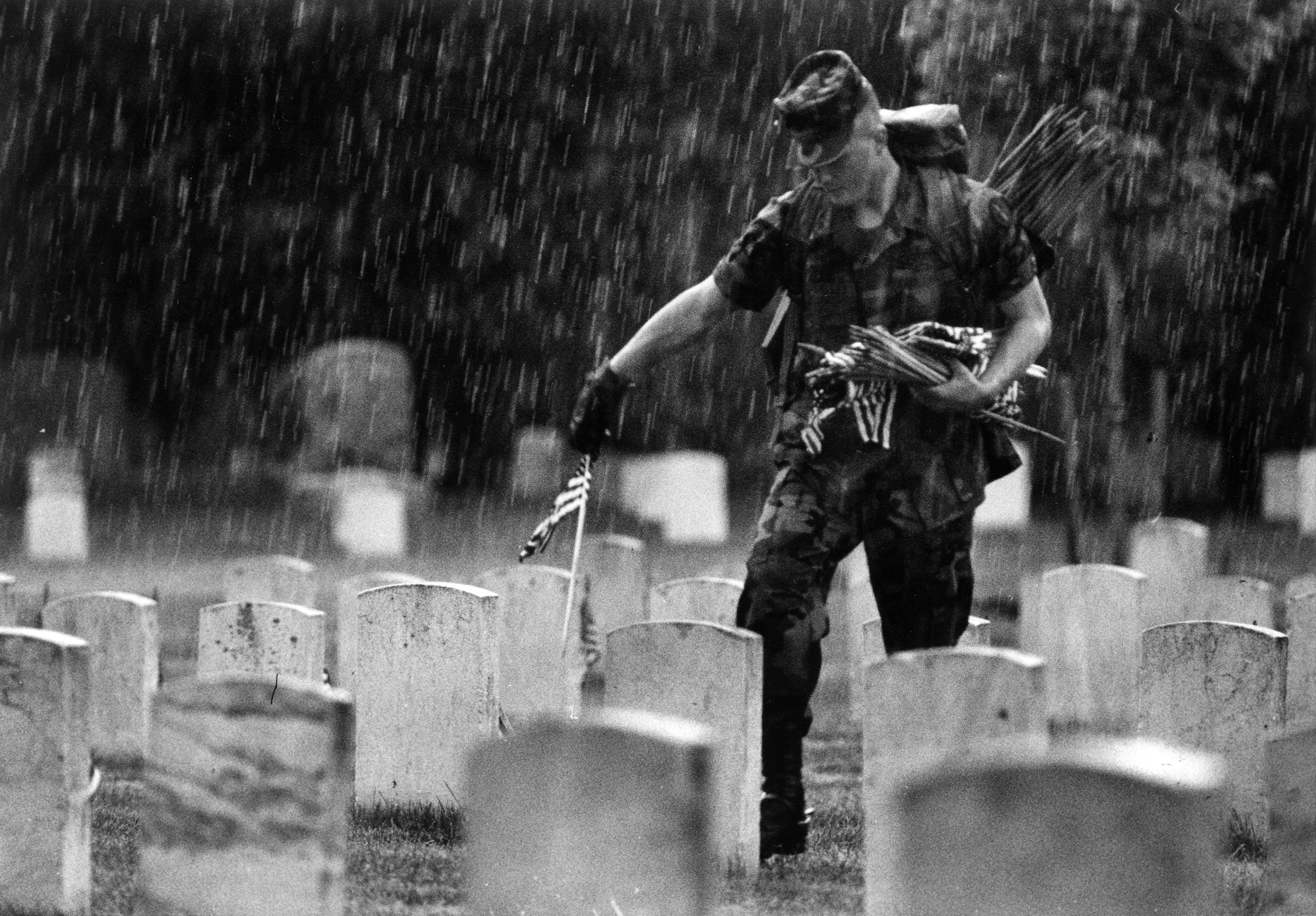 Undaunted by the downpour, a private walks amongst the headstones planting flags in Arlington National Cemetery in Va. on May 25, 1995.