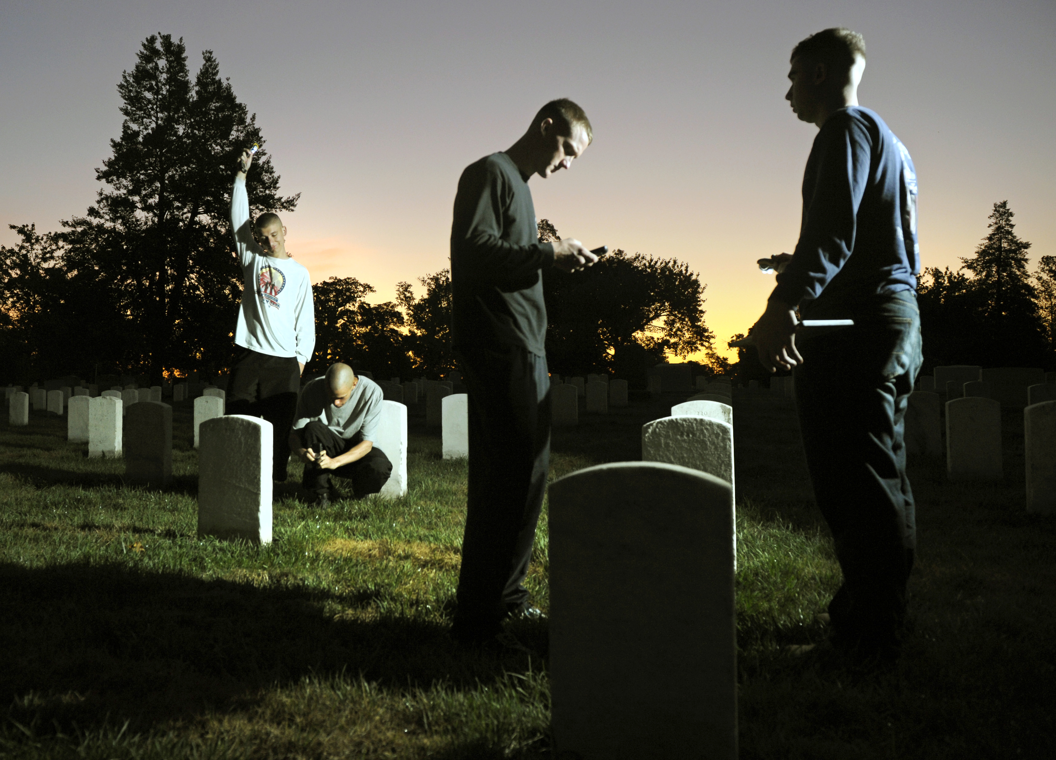 As the sun rises, soldiers from the Army Old Guard photograph headstones in Section 15 of Arlington National Cemetery as part of Task Force Christman to photograph and catalog more than 219,00 grave markers and the front of more than 43,000 sets of cremated remains at Arlington National Cemetery in Va., Aug. 24, 2011.