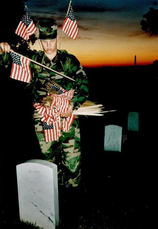 U.S. Army Specialist Brian Murphy places U.S. flags on grave markers as day breaks at Arlington National Cemetery in Va., May 22, 1992.