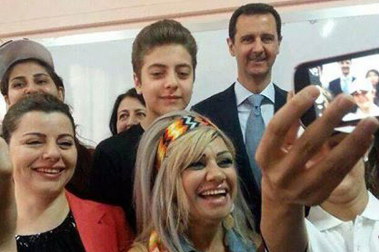 This handout picture released by the official Facebook page of Syria's First Lady Asma al-Assad shows Syrian President Bashar al-Assad (R) posing for a selfie with a group of youths after casting his vote at a polling station in Maliki, a residential area in the centre of the capital Damascus, in the country's presidential elections on June 3, 2014.