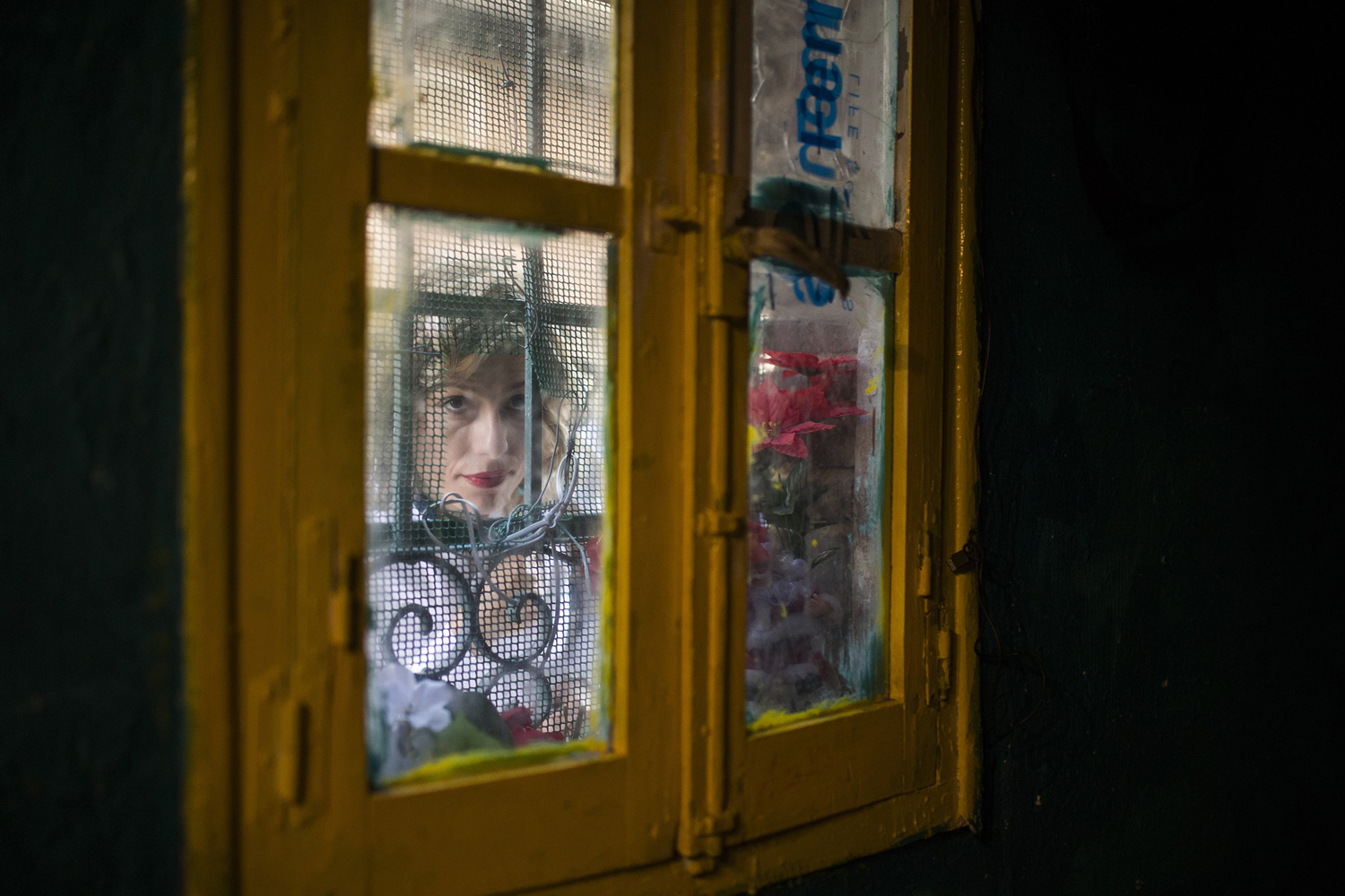 Jun. 17, 2014.  A neighbour of Gabriela Ovid checks to see if the family are still in the house as she arrives to help them during Ovid's eviction in Madrid, Spain.