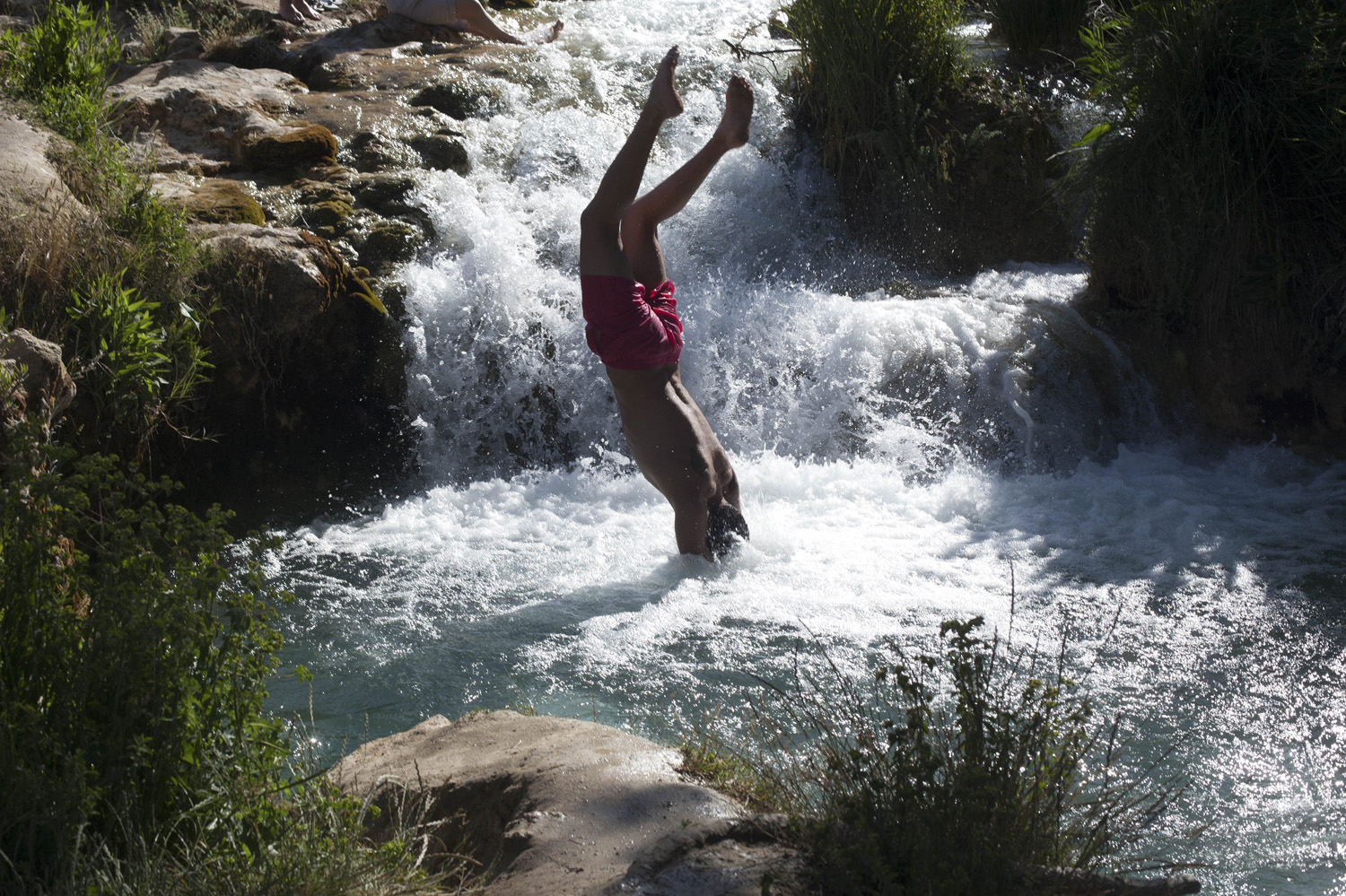 A youth dives into a natural rock pool in the Lagoons of Ruidera Natural Park in Ruidera, Spain,  June 8, 2014.