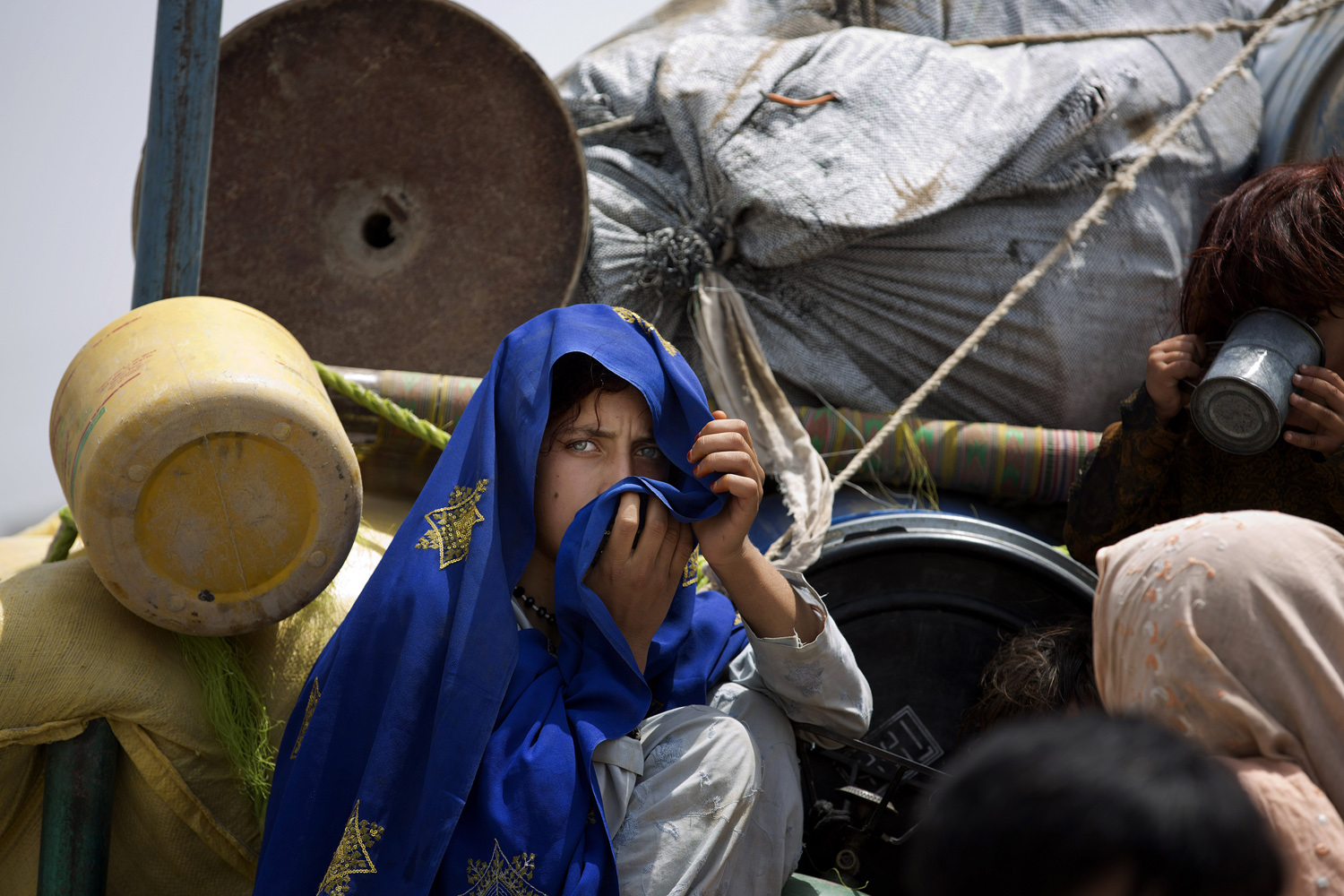 Jun. 18, 2014. A Pakistani tribal girl sits next to her belongings on a truck after arriving to Bannu, Pakistan. Thousands of villagers fled as Pakistani army relax a curfew in troubled North Waziristan.