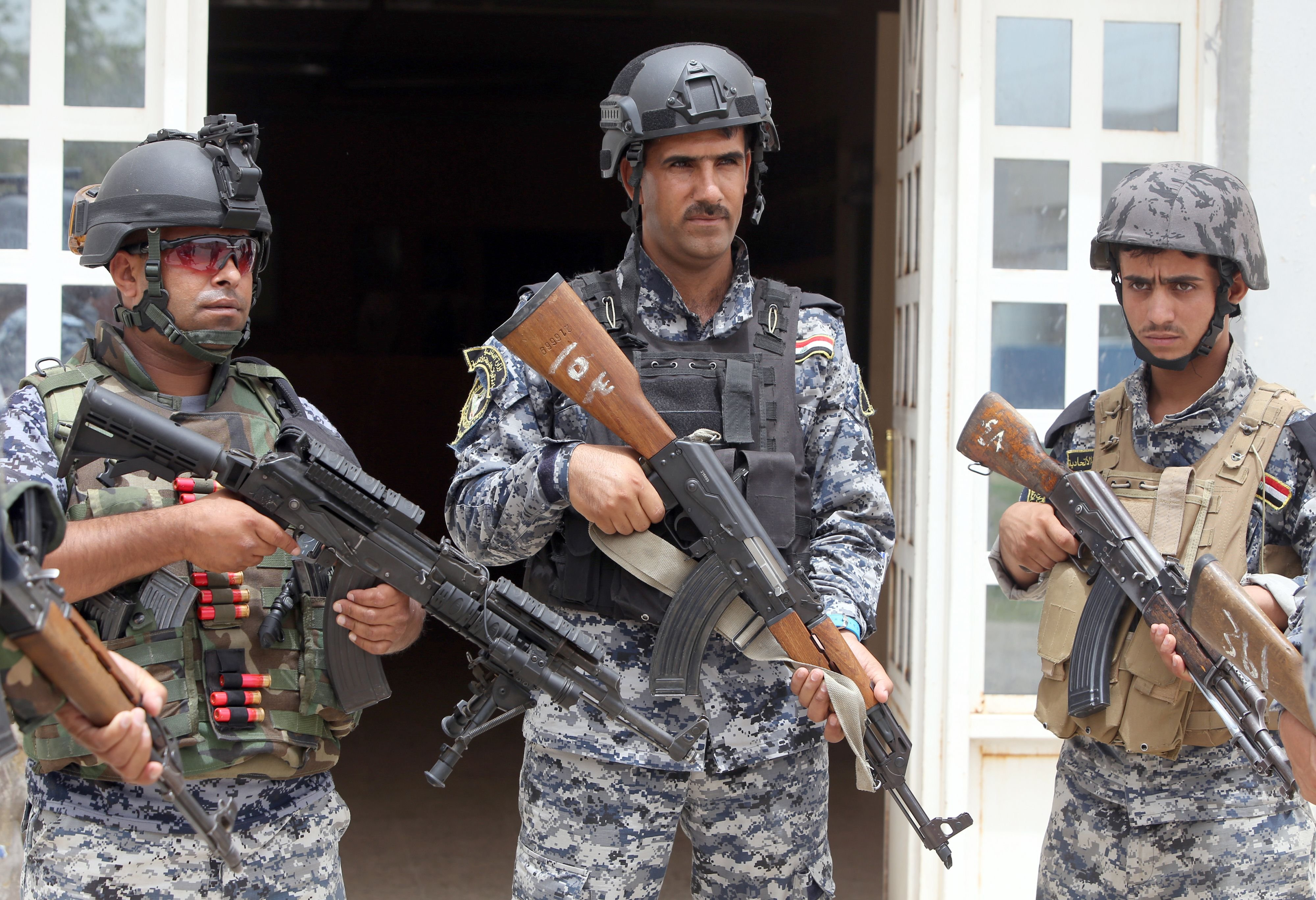 Iraqi policemen listen to a briefing inside a military base in the capital Baghdad, on June 11, 2014, after the declaration of a state of emergency by the government.