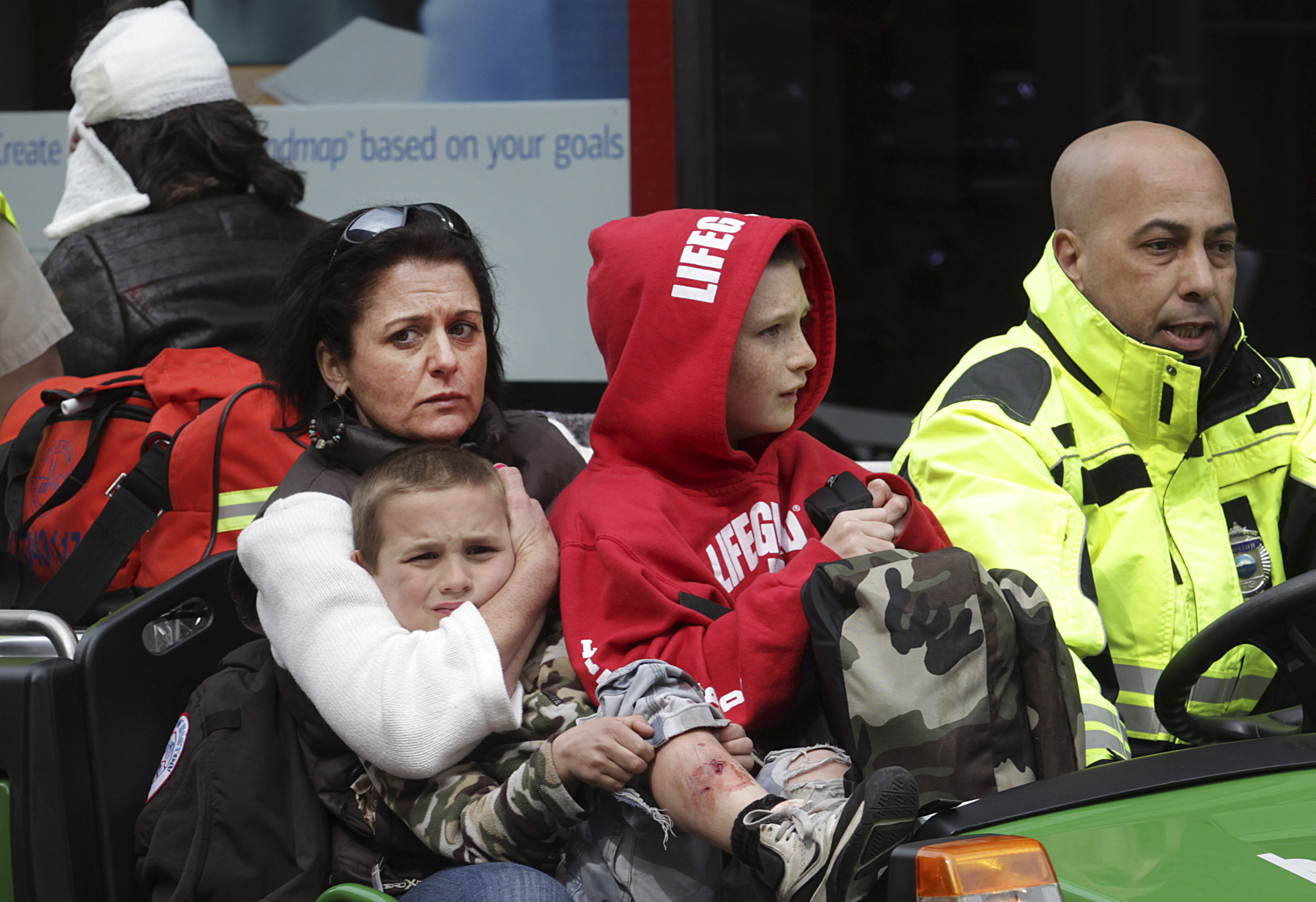 Women and children are evacuated from the scene on Boylston Street after two explosions went off near the finish line of the 117th Boston Marathon on April 15, 2013.
