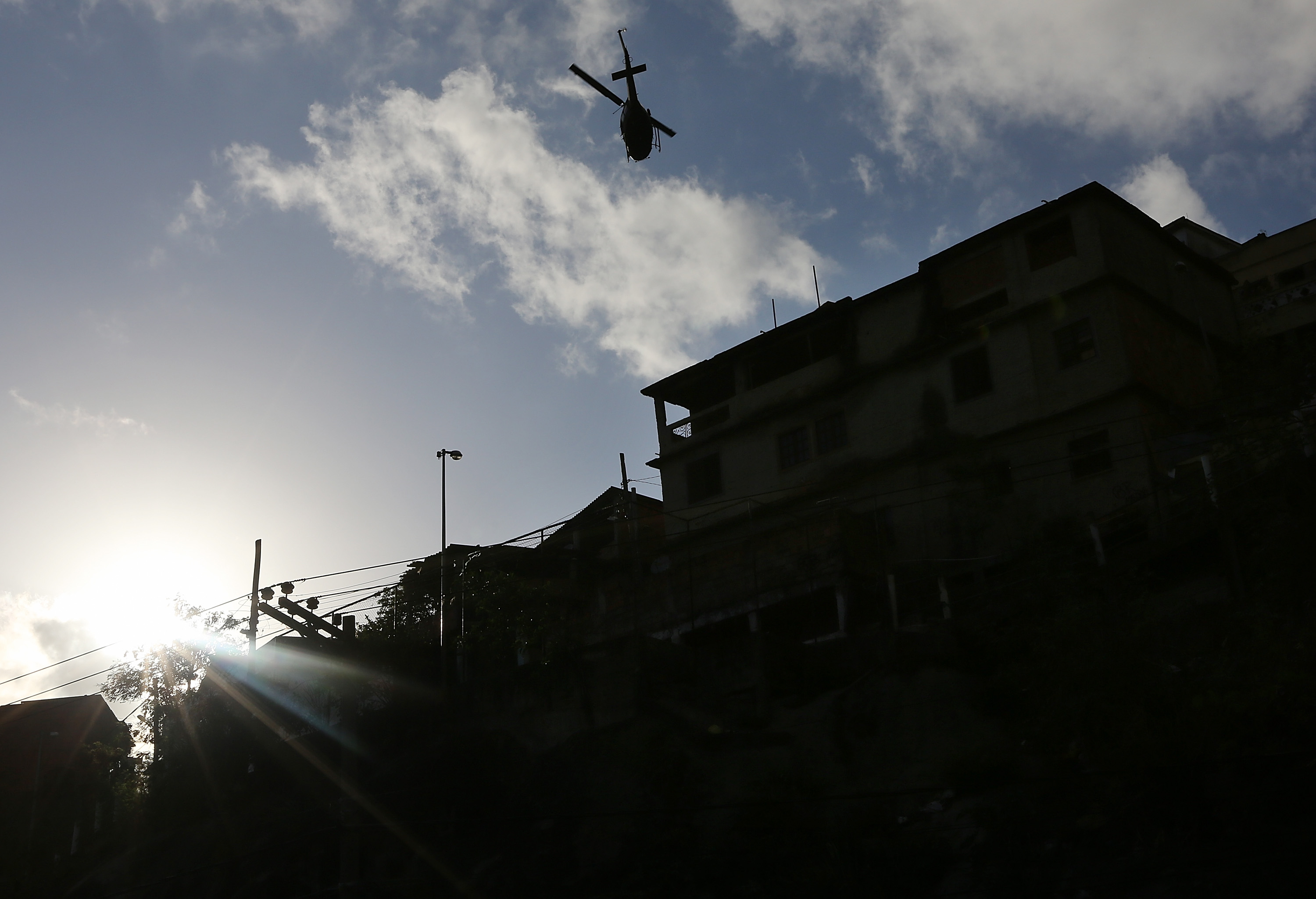 A military helicopter flies overhead  during a 'pacification' operation in the favela complex of Lins de Vasconcelos, in the North Zone, on October 6, 2013 in Rio de Janeiro.