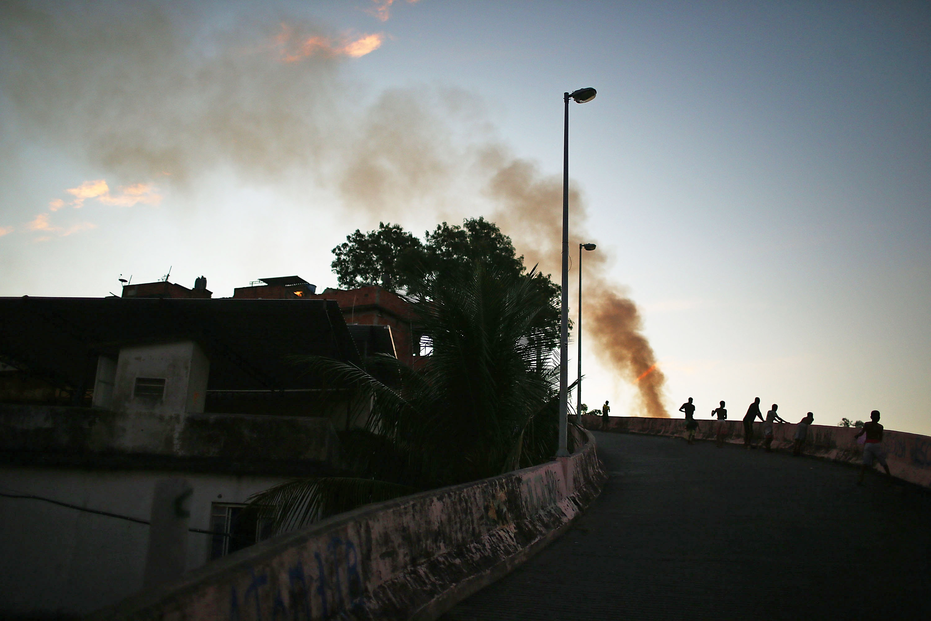 Kids look over a ledge as a trash fire burns in the Mangueira favela which overlooks the famed Maracana Stadium on June 5, 2014 in Rio de Janeiro.
