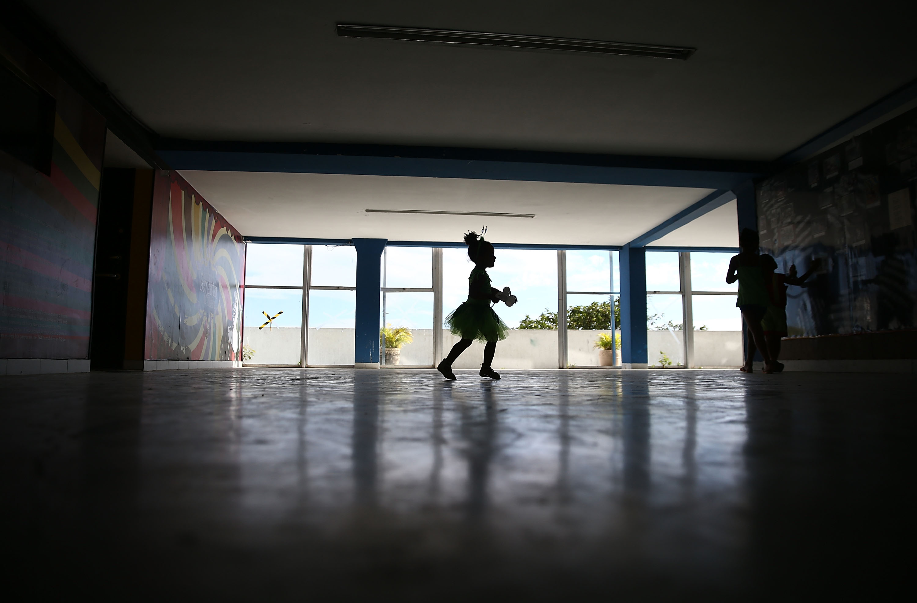 A young reveler runs during pre-Carnival festivities in the Cantagalo shantytown community next to neighboring Pavao-Pavaozinho on February 22, 2014 in Rio de Janeiro.