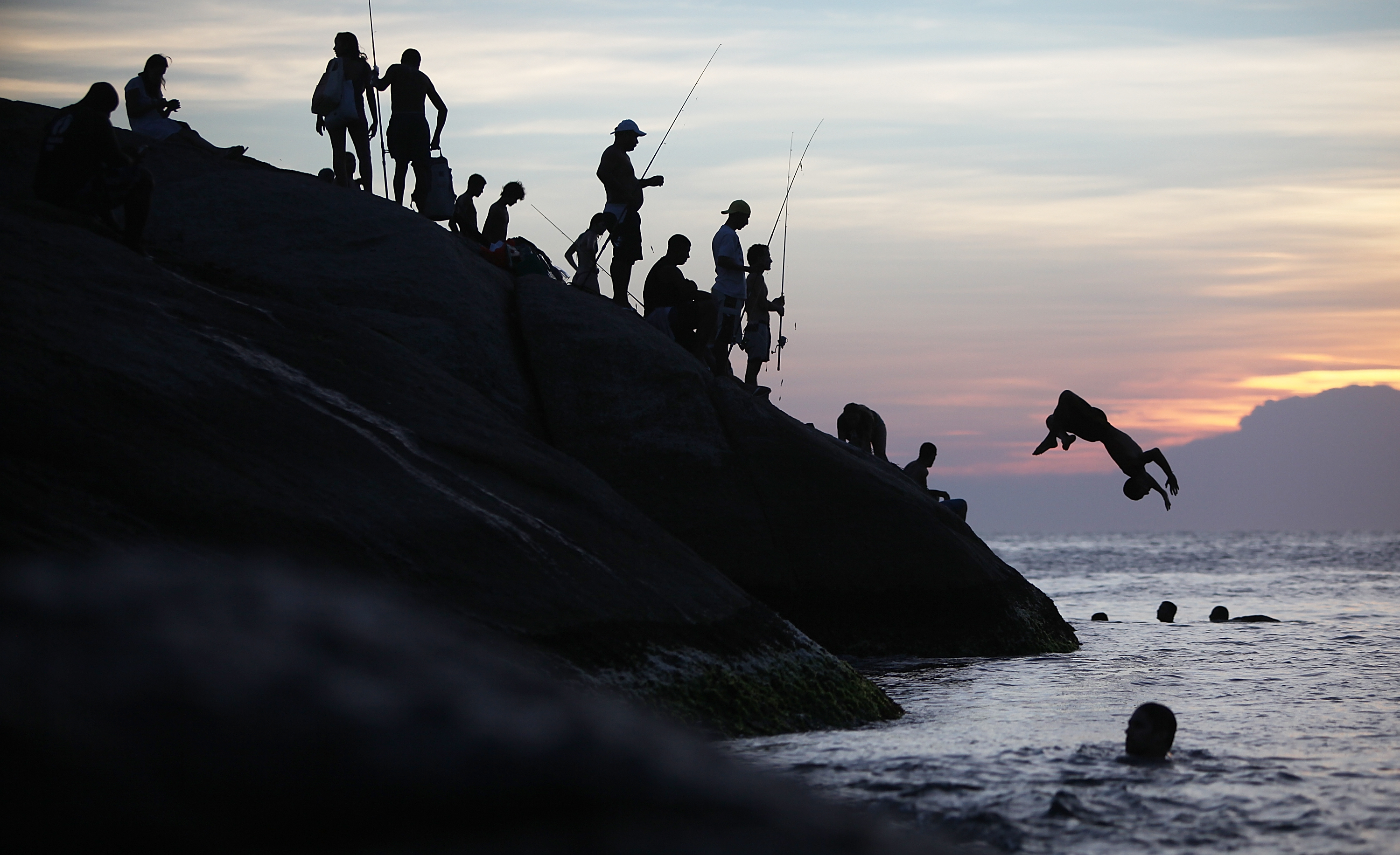 A man flips off the rocks at Arpoador at sunset during a summer heat wave in the city on January 3, 2014 in Rio de Janeiro.