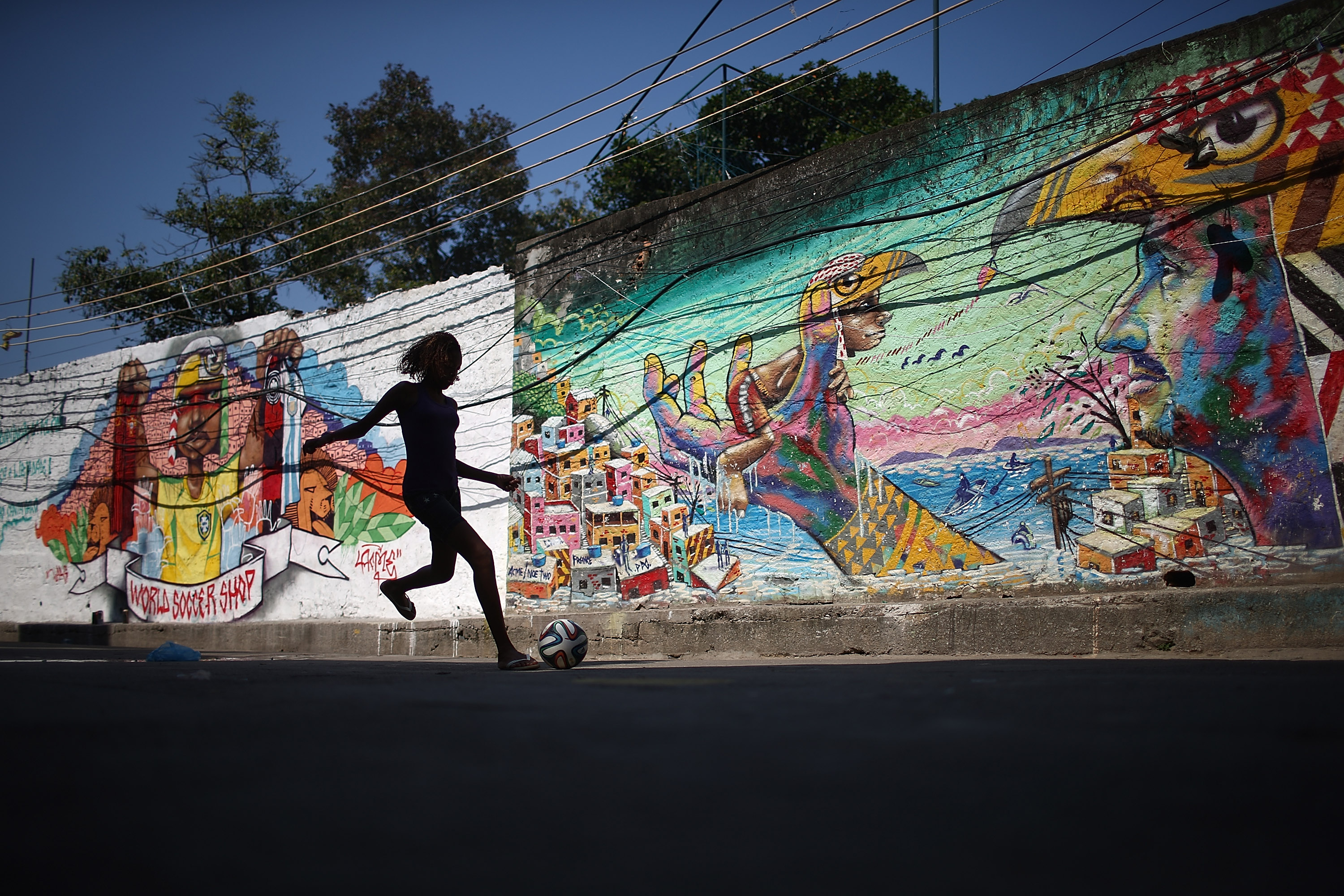 A girl plays soccer in front of graffiti created by acclaimed local graffiti artist Acme in the pacified Pavao-Pavaozinho community, on May 8, 2014 in Rio de Janeiro.