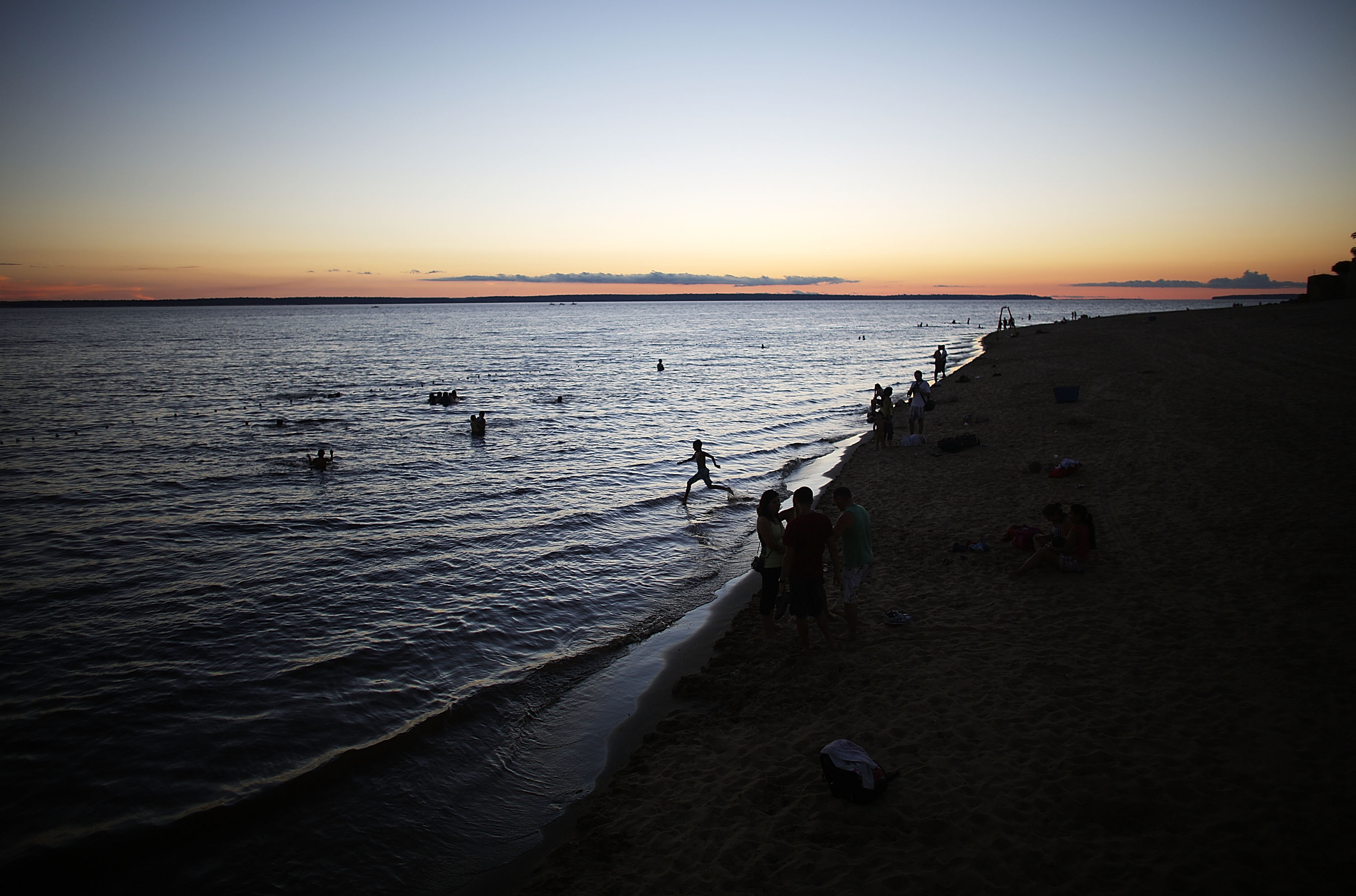 People gather at Ponta Negra beach on Rio Negro, a branch of the Amazon River, on November 23, 2013 in Manaus, Brazil.