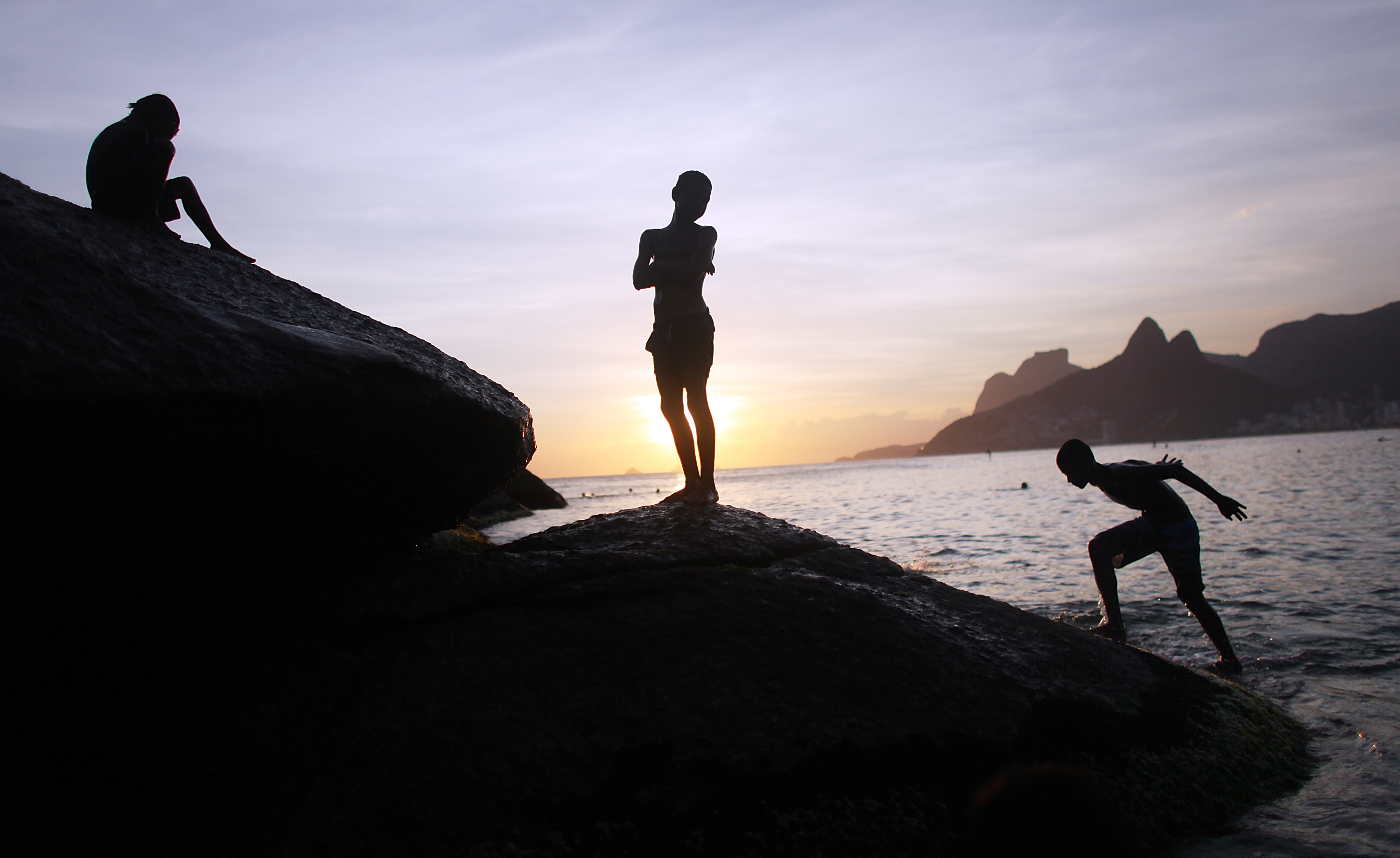 Kids play on the rocks at Arpoador at sunset during a summer heat wave in the city on January 3, 2014 in Rio de Janeiro.