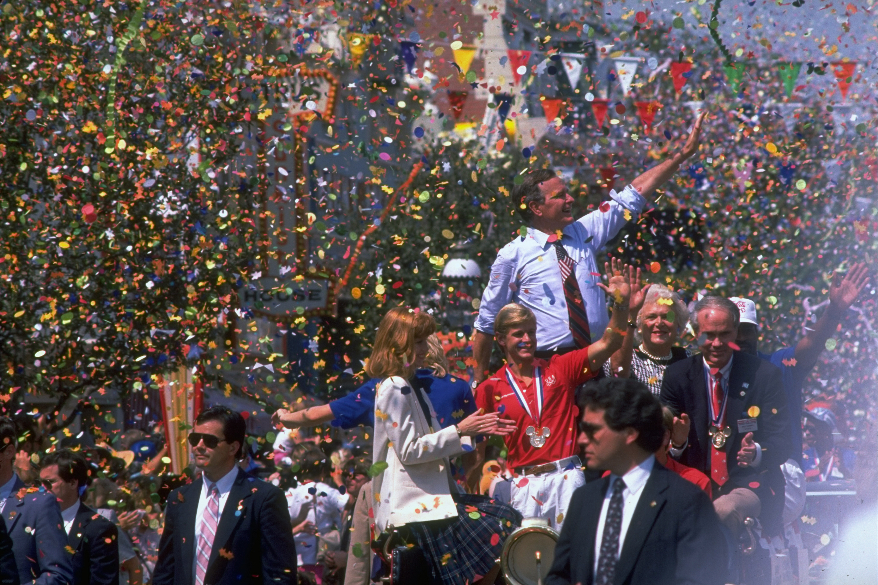 Republican presidential candidate George H.W. Bush waving above a crowd amid shower of parade confetti, with wife Barbara by his side  at a send-off gala for the US Olympic team.