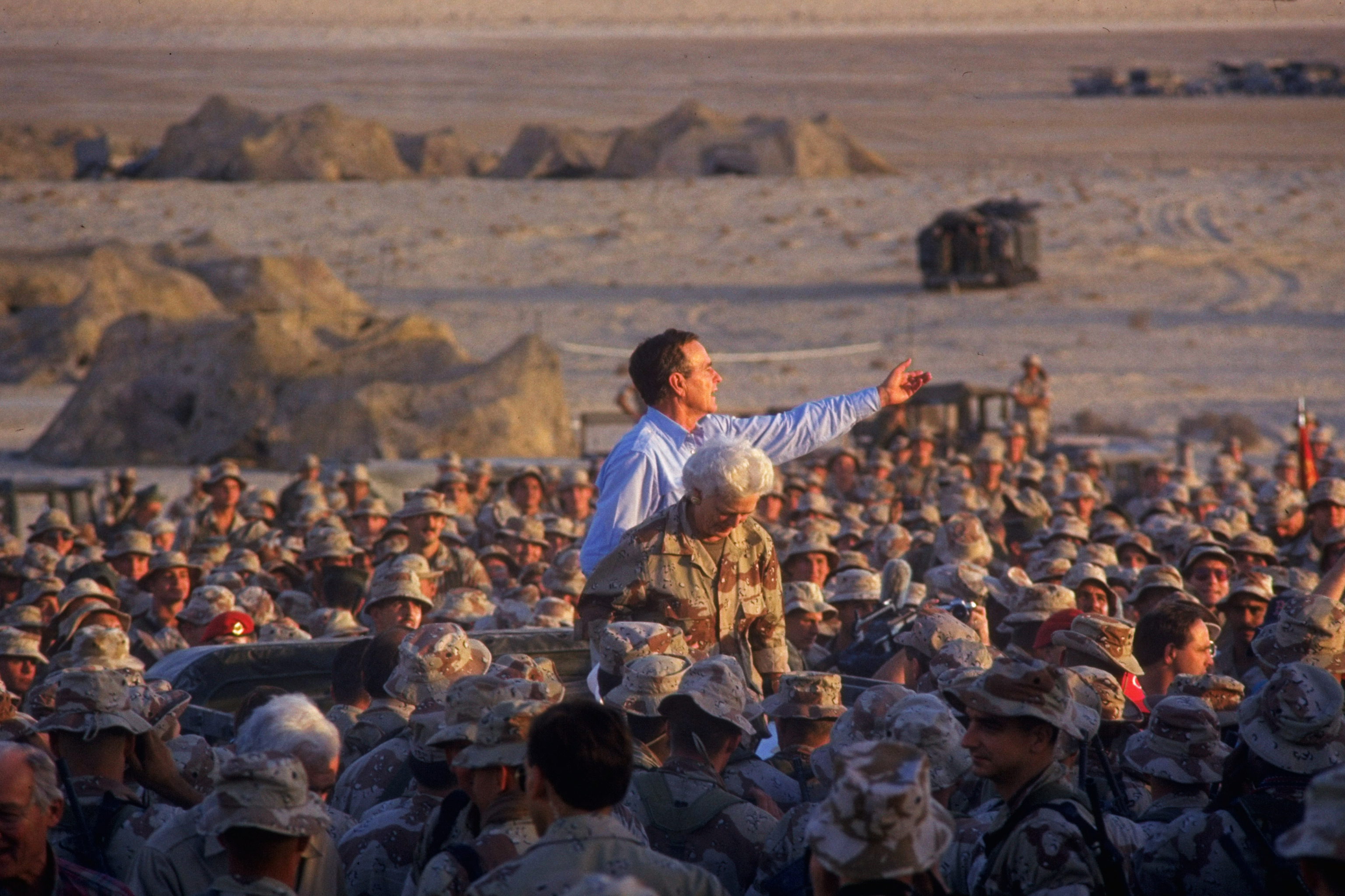 President George H.W. Bush and Barbara Bush poised above a crowd of First Marine Division Desert Command Post marines on thanksgiving during the Gulf Crisis on November 22, 1990.