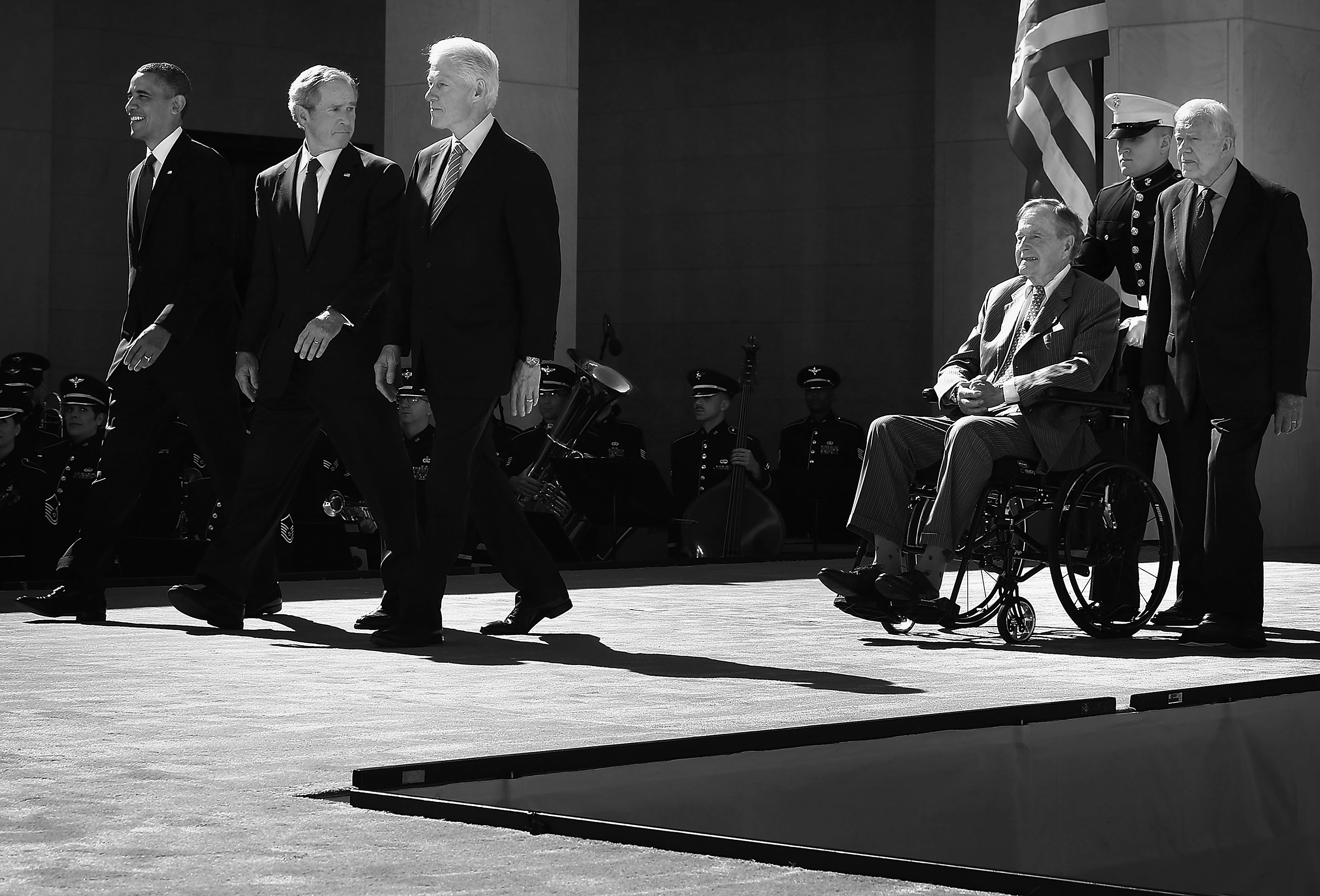 Former U.S. President George W. Bush turns around and checks on his father and former President George H.W. Bush as all five living presidents, including Barack Obama, Bill Clinton and Jimmy Carter, come out on stage during the opening ceremony of the George W. Bush Presidential Center on April 25, 2013 in Dallas, Texas.