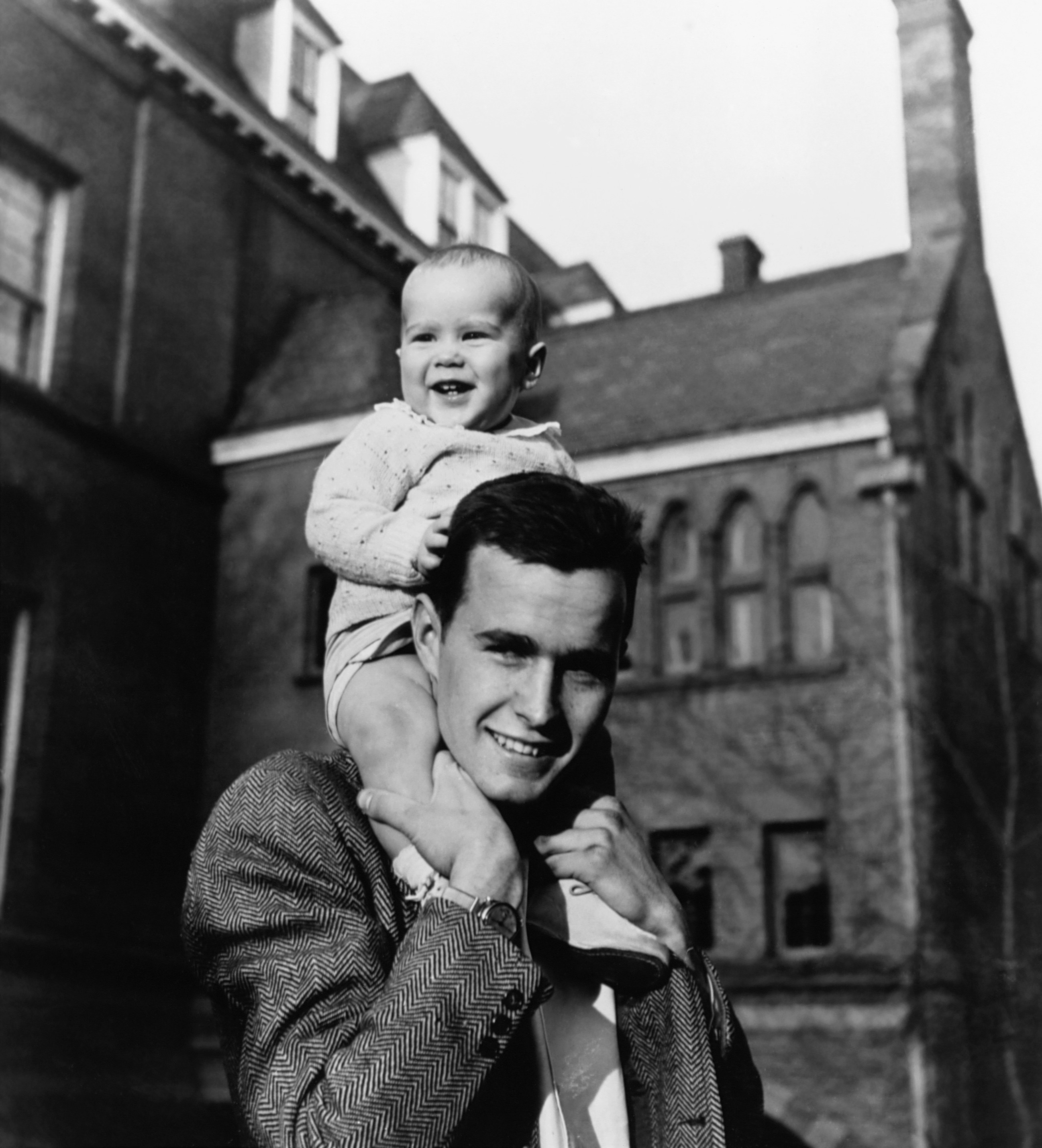 George H.W. Bush carries his infant son George W. Bush on his shoulders at Yale University in New Haven, Conn.