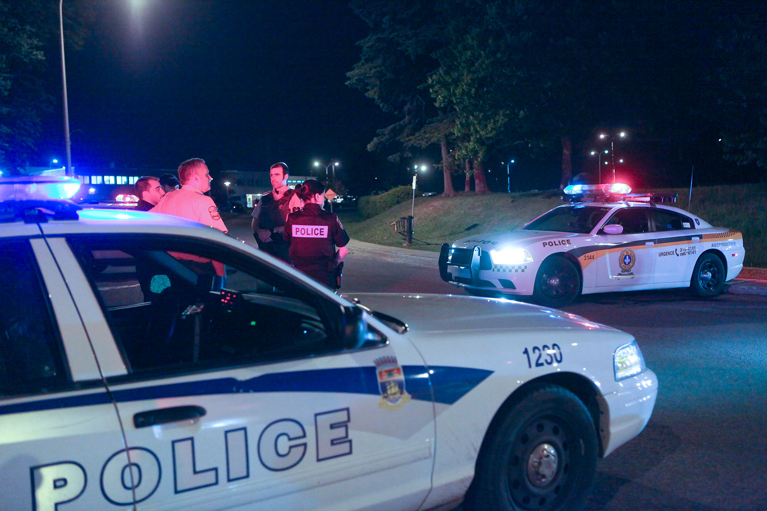 Police cars are seen in front of the Orsainville Detention Center near Quebec City on Saturday, June 7, 2014. Three inmates have escaped from the center with the help of a helicopter, police said late Saturday.