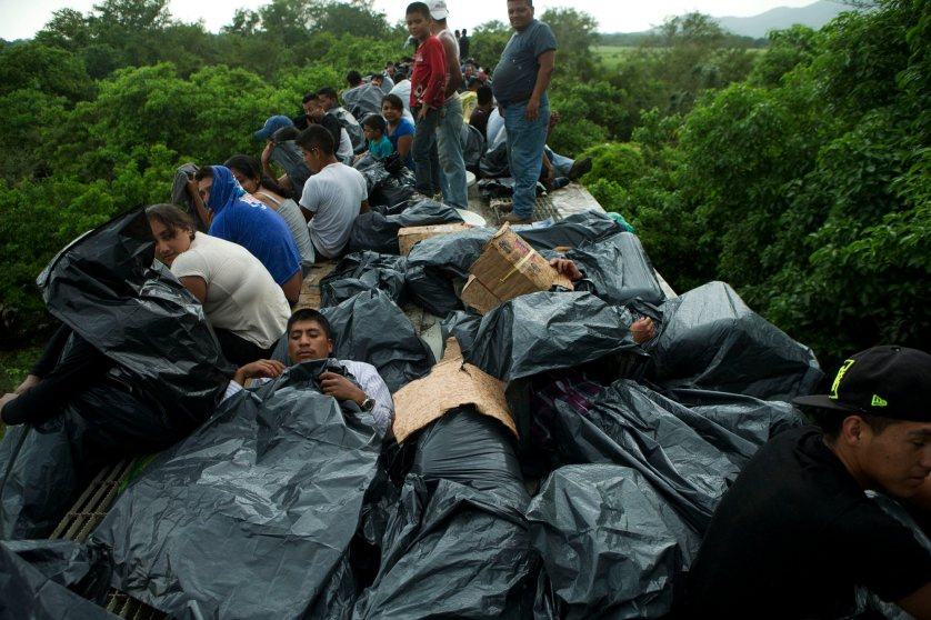 Central American migrants use trash bags and cardboard to protect themselves from the rain as they wait atop a stuck freight train, outside Reforma de Pineda, Chiapas state, Mexico, June 20, 2014.