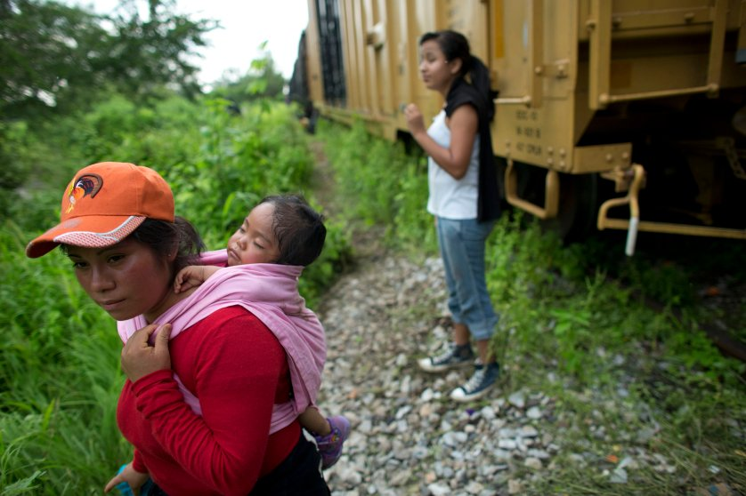 Guatemalan migrant Gladys Chinoy, 14, right, waits with more than 500 other migrants, many traveling with small children, beside the stuck freight train on which they were traveling, outside Reforma de Pineda, Chiapas state, Mexico, June 20.