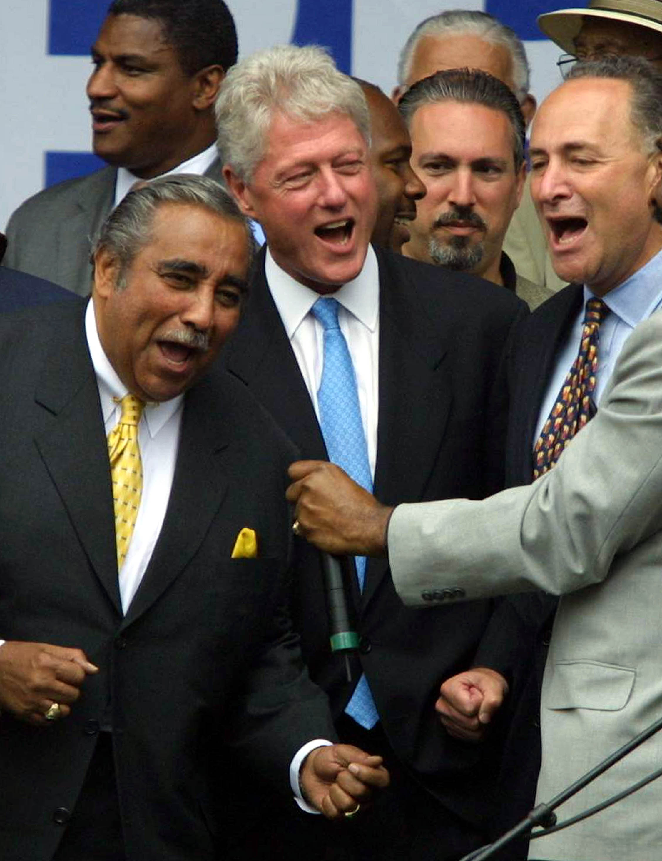 Former U.S. President Bill Clinton sings with U.S. Rep. Charles Rangel, left, and U.S. Sen. Charles Schumer, right, in the Harlem neighborhood of New York City, July 30, 2001.