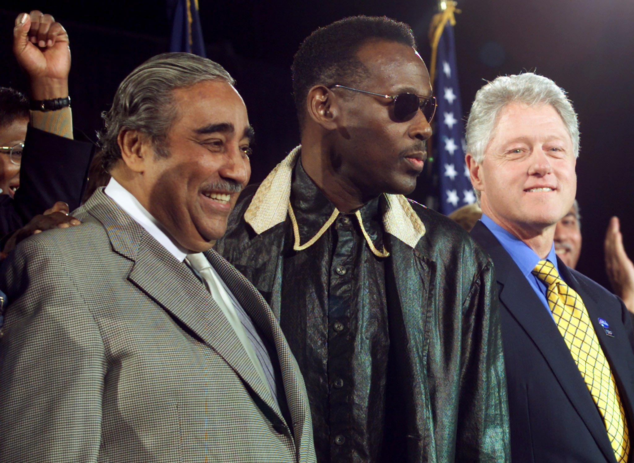 U.S. President Bill Clinton waits to speak to a Democratic rally in the Harlem neighborhood of New York City with Congressman Charles Rangel (D-NY) (L) and singer Luther Vandross (C), Nov. 4, 2000.