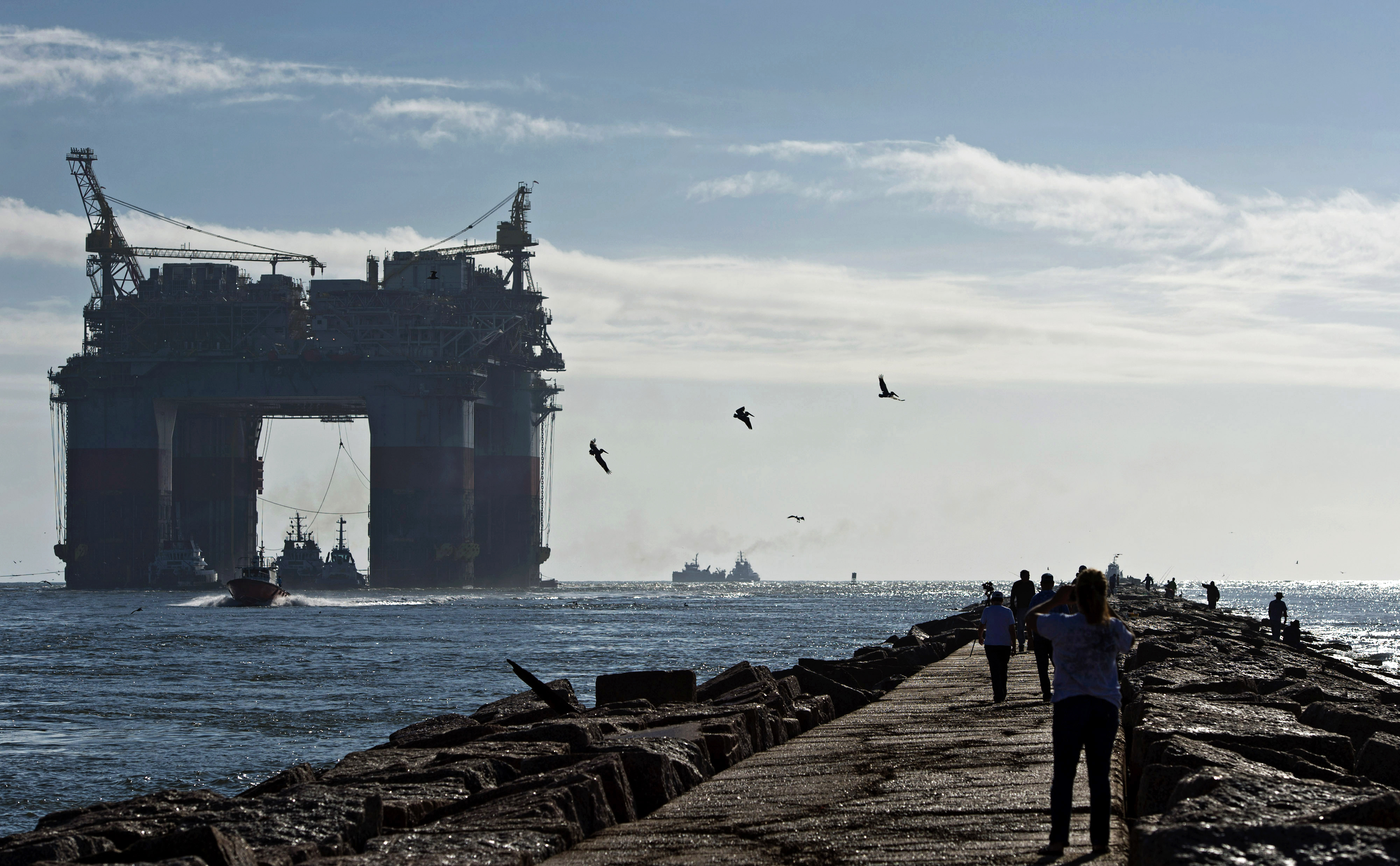 Birds fly as pedestrians watch tug boats transport the Chevron Corp. Jack St. Malo semi-submersible drilling and production platform to the Gulf of Mexico from Kiewit Offshore Services in Ingleside, Texas, U.S., on Nov. 15, 2013.
